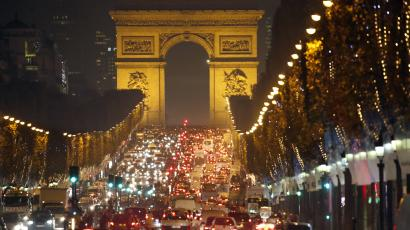 Christmas holiday lights decorate trees along the Champs Elysees with its Arc de Triomphe, in Paris November 20, 2014.