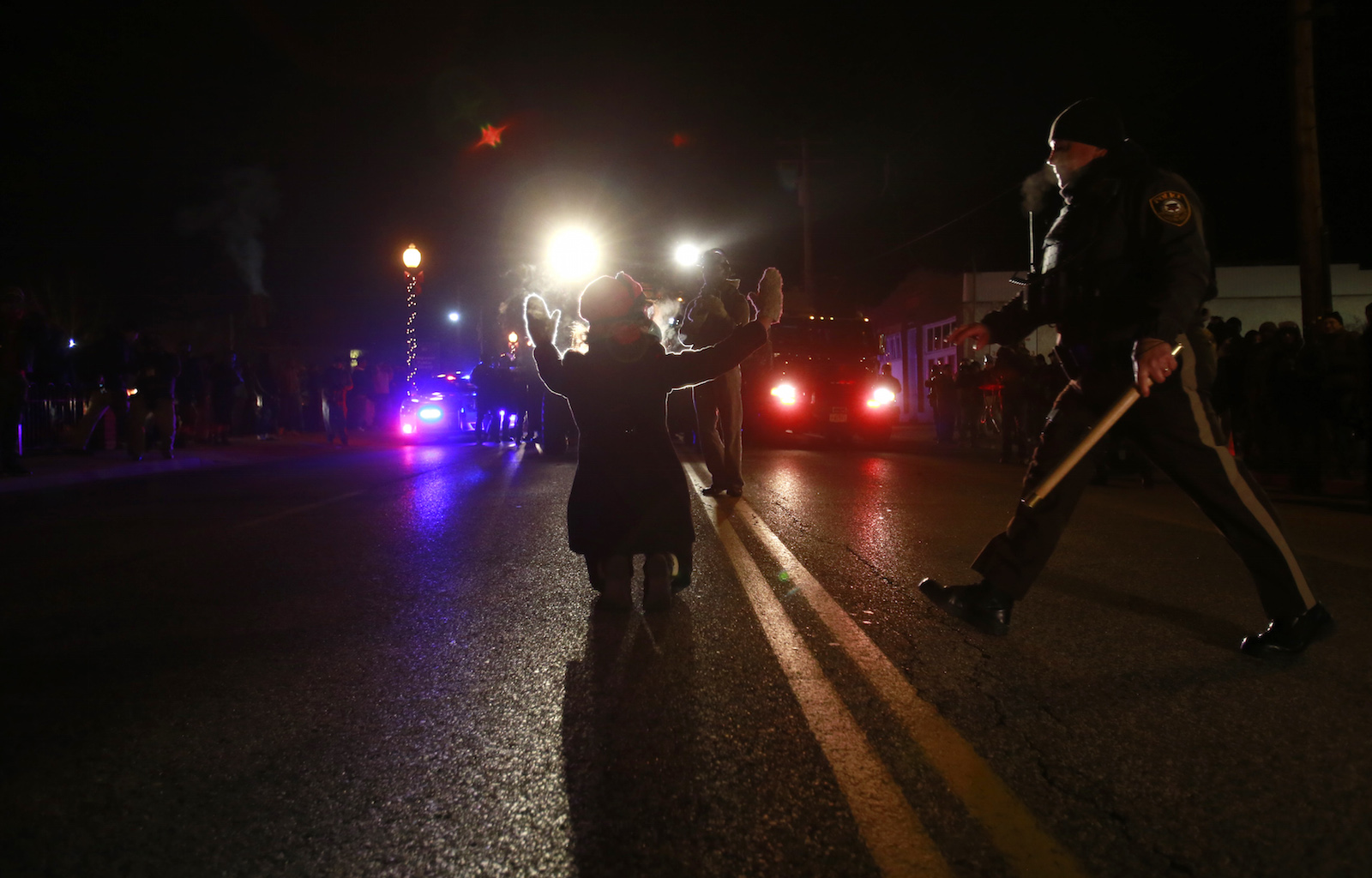 A police officer (R) moves in to arrest a protester on her knees in front of police cars in Ferguson, Missouri, November 25, 2014. Missouri's governor ordered hundreds more National Guard troops to the St. Louis suburb rocked by rioting after a white policeman was cleared in the fatal shooting of an unarmed black teenager REUTERS/Adrees Latif