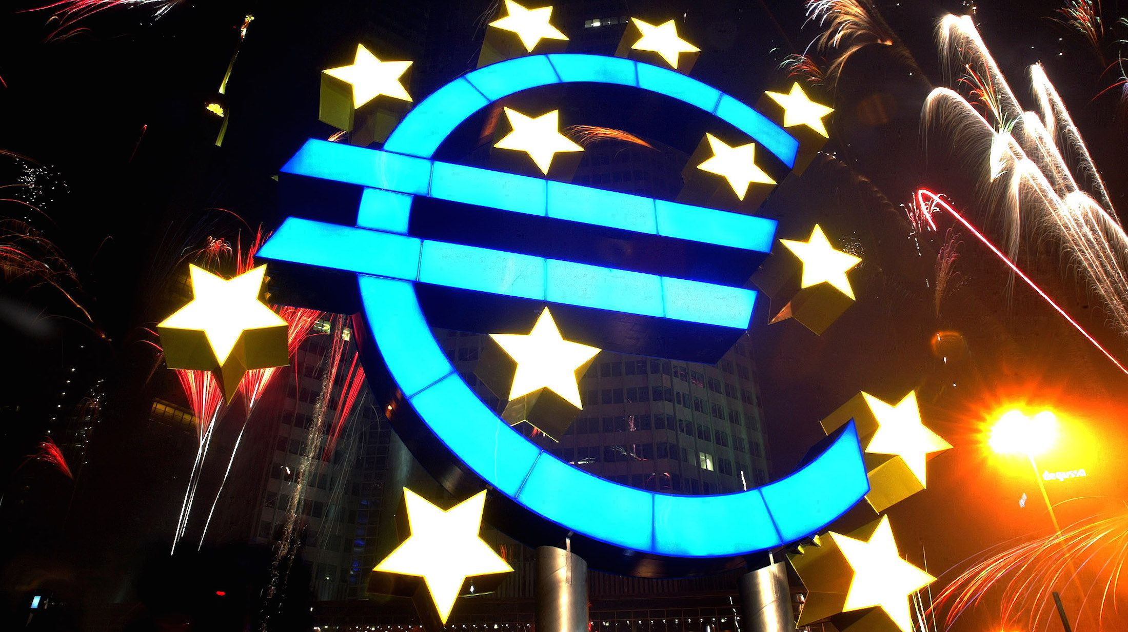 Fireworks illuminate the sky around a huge euro sculpture, designed by German artist Ottmar Hoerl, in front of the headquarters of the European Central Bank (ECB) in Frankfurt, January 1, 2002. Several thousand people in Frankfurt celebrated at a party on the streets around the ECB to welcome Europe's new currency, the euro. UNICS REUTERS/Kai Pfaffenbach REUTERS  KP - RTRBPKK