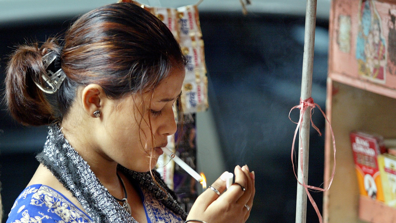 An Indian girl lights up a cigarette at a street side kiosk in Bombay May 7, 2004. In one of Asia's most polluted cities, most people fail to see the point of a ban on smoking - but some are fuming. The Indian Tobacco Bill, which took effect on May 1, imposes a ban nationwide ban on smoking in public places, advertising of tobacco products in mass media - except at point of sale - and selling to anyone under the age of 18. Picture taken on May 7, 2004. FOR RELEASE WITH FEATURE INDIA TOBACCO BAN REUTERS/Arko Datta AH/