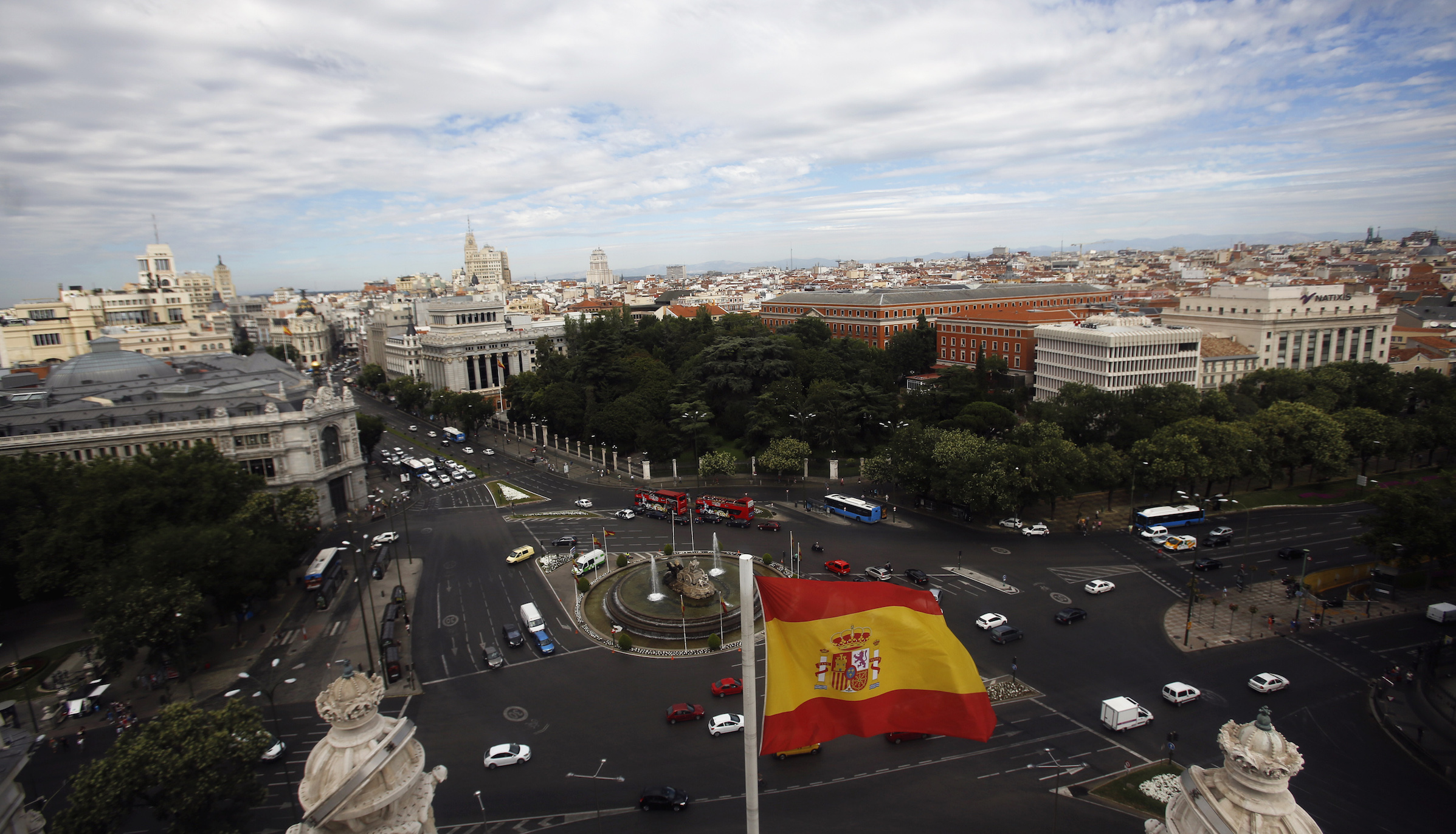 A Spanish flag flutters in the air as the capital of Spain is seen from the observatory deck of Madrid's city hall August 7, 2013.  REUTERS/Sergio Perez (SPAIN - Tags: CITYSCAPE TRAVEL) - RTX12COK