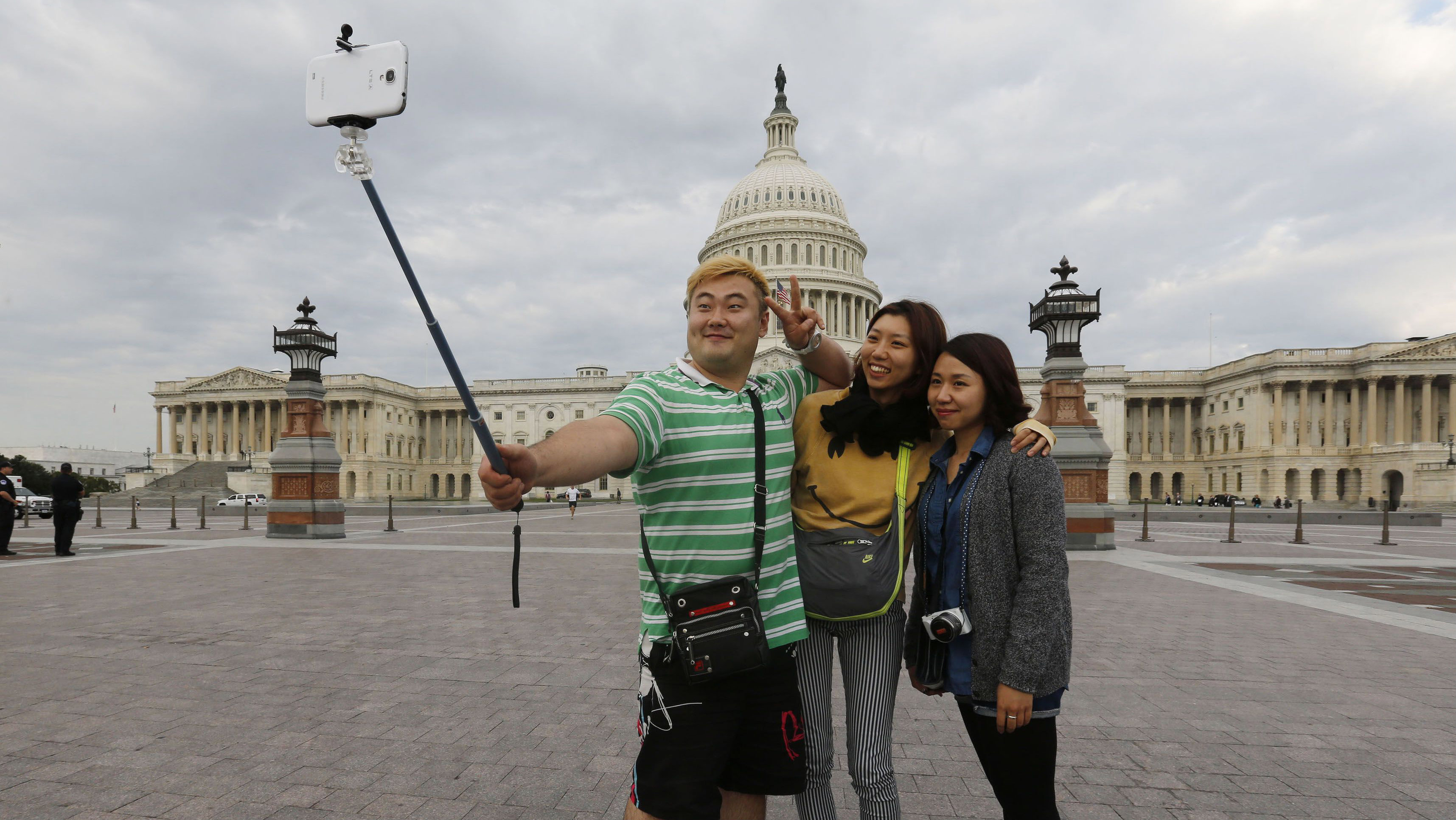 South Korean tourists (L-R) Heemok Ann, Eunyi Ji, and Mijung Jung take their own picture in front of the U.S. Capitol dome on Capitol Hill in Washington after the U.S. government shutdown, October 1, 2013. The U.S. government began a partial shutdown on Tuesday for the first time in 17 years, potentially putting up to 1 million workers on unpaid leave, closing national parks and stalling medical research projects. REUTERS/Larry Downing