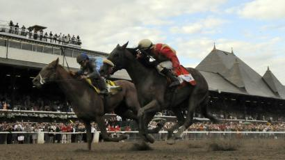 V.E. Day, left, with jockey Javier Castellano up, moves past Wicked Strong right, with jockey Rajiv Maraghto up, to win the Travers Stakes horse race at Saratoga Race Course in Saratoga Springs, N.Y., Saturday, Aug. 23, 2014. (AP Photo /Hans Pennink)