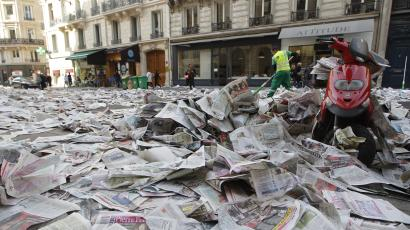 sweeping newspapers off the street