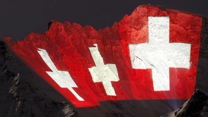 A giant light installation of the flag of Switzerland, by Swiss artist Gerry Hofstetter, illuminates the north face of the Jungfrau in the Bernese Oberland January 12, 2012. The installation commemorates the 100-year anniversary of the Jungfrau railway, which first began operations in the year 1912. The light left of the installation is Europe's highest railway station, the Jungfraujoch station, at an altitude of 3,454 metres (11,332 ft). REUTERS/Arnd Wiegmann (SWITZERLAND - Tags: TRAVEL SOCIETY ANNIVERSARY)