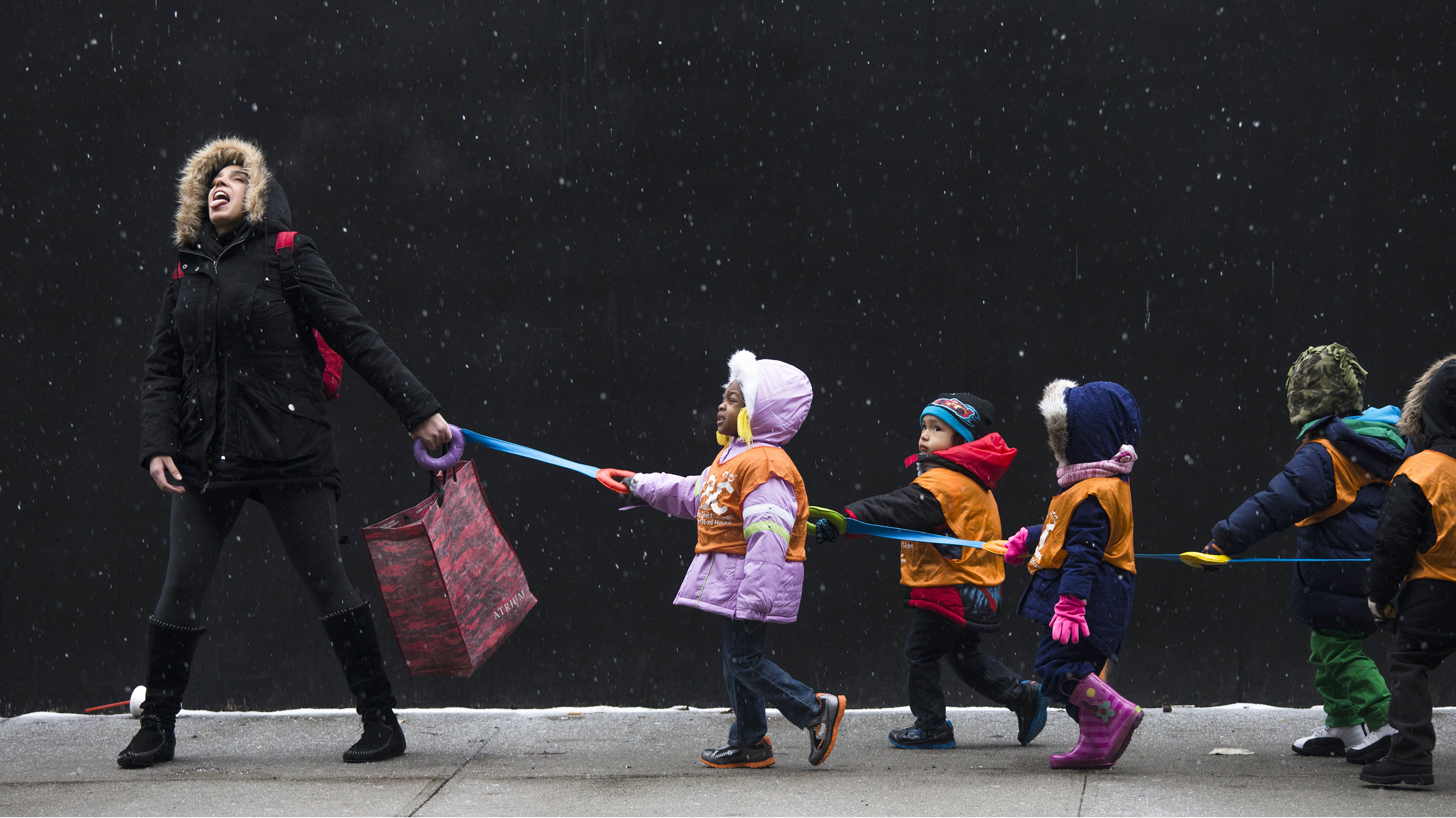 A schoolteacher, who wished to stay unidentified, attempts to catch snowflakes while leading her students to a library from school in the Harlem neighborhood, located in the Manhattan borough of New York on January 10, 2014.