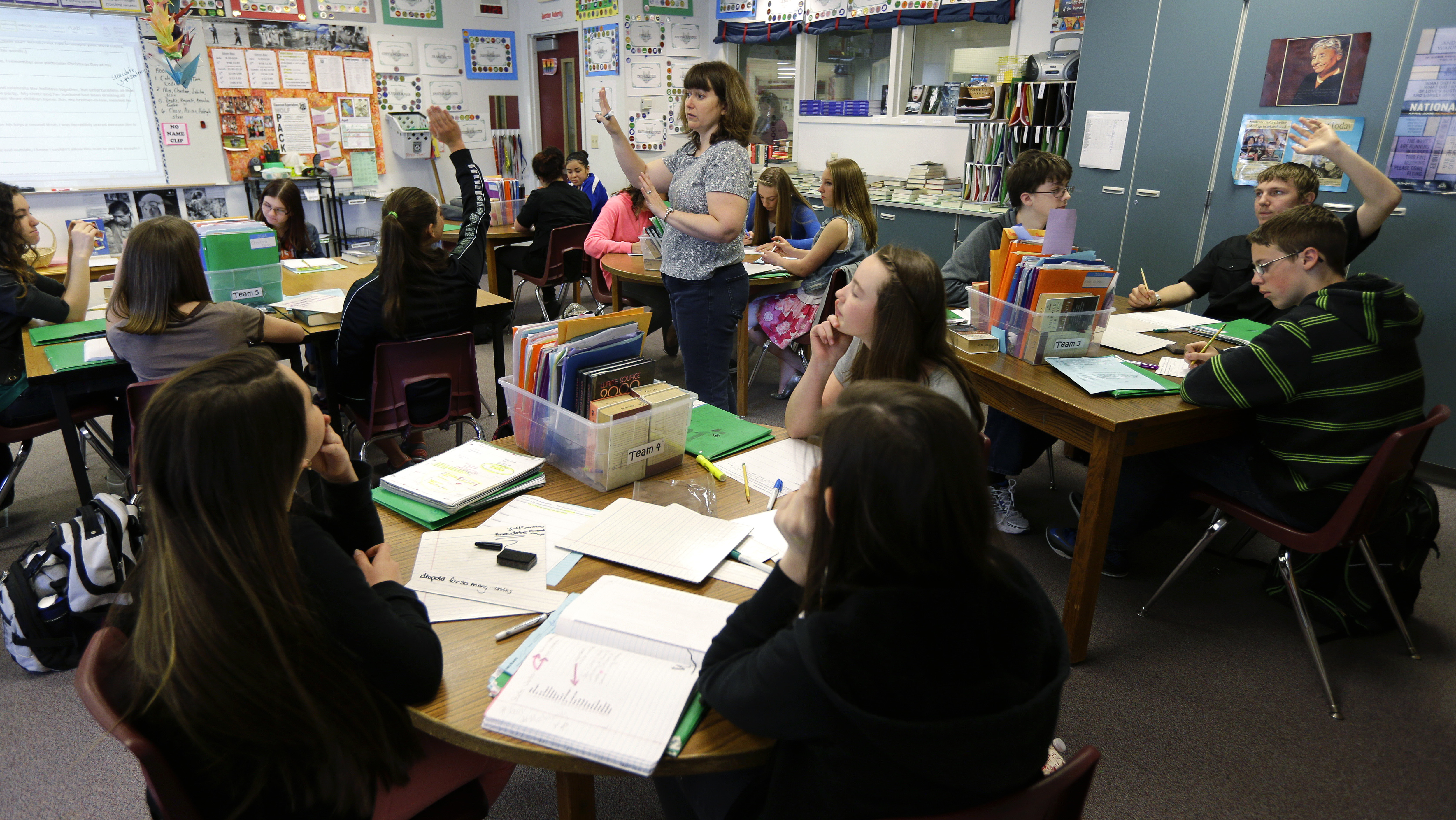 In this April 18, 2014 photo, Annette Wells, center, takes questions in her 7th-8th grade language arts class at Komachin Middle School in Lacey, Wash. Wells has switched from desks to tables due to the number of students she needs to fit in her classroom. An Associated Press analysis of Washington school enrollment data shows 136 school districts, out of 295, added students between the 2011-12 school year and the current academic year. (AP Photo/Ted S. Warren)
