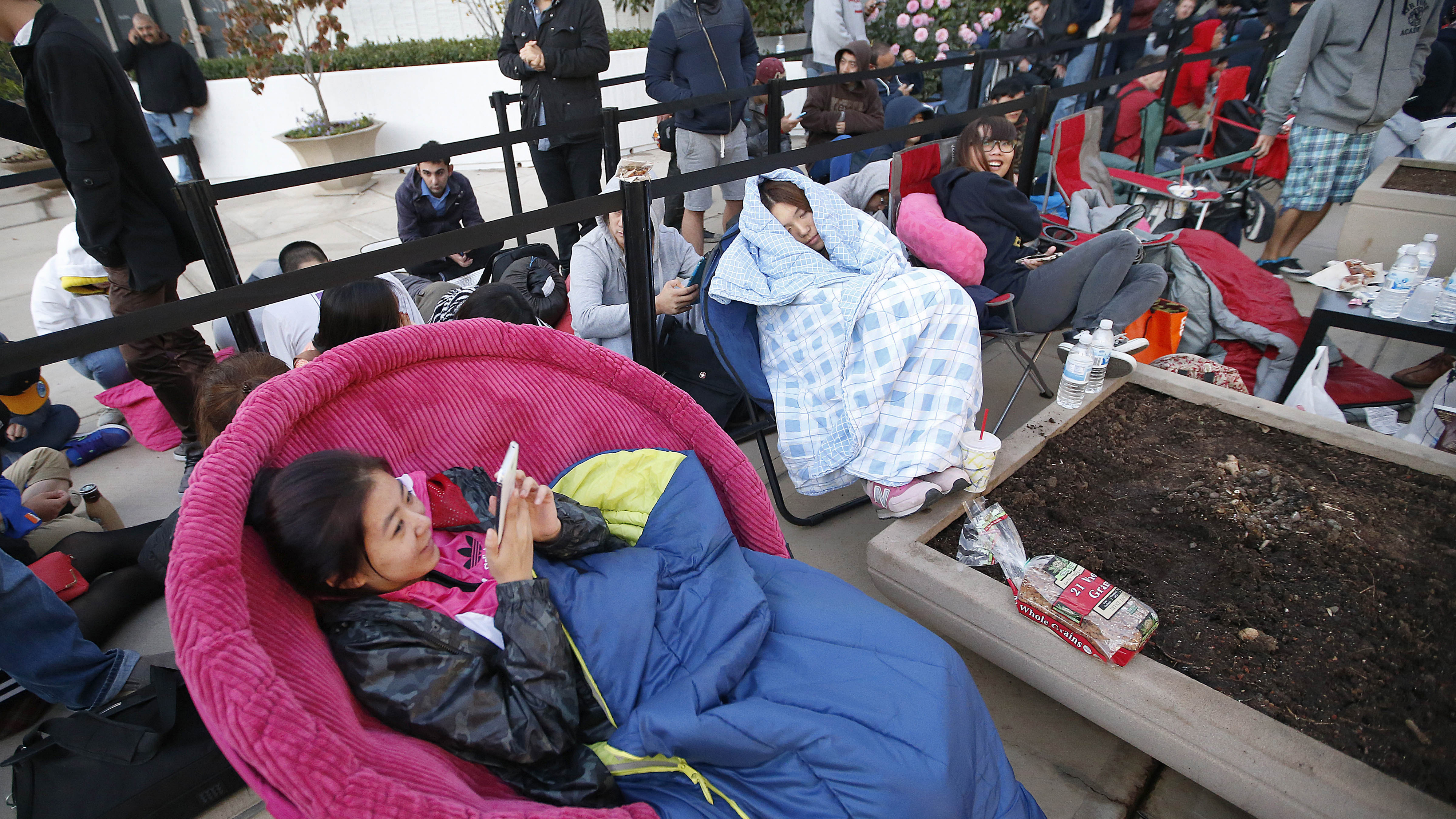 Yuki Lau, left, and friend Jianing Hong, center, wait in line for the opening of the Apple Store for the launch and sale of the new iPhone 6 on Friday, Sept 19, 2014 Palo Alto, Calif. (AP Photo/Tony Avelar)