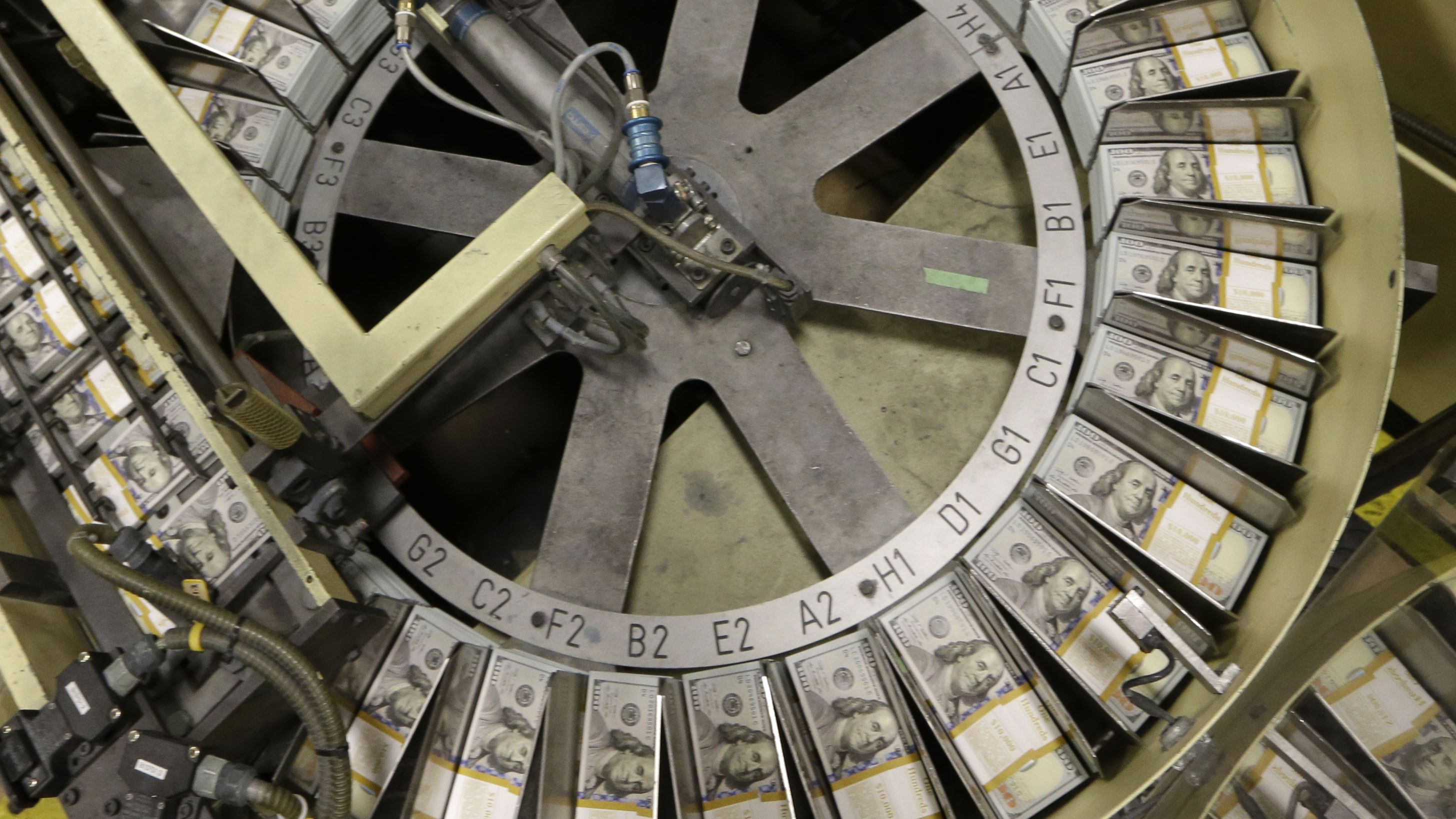 ust cut stacks of $100 bills make their way down the line at the Bureau of Engraving and Printing Western Currency Facility in Fort Worth, Texas, Tuesday, Sept. 24, 2013. (AP Photo/LM Otero)