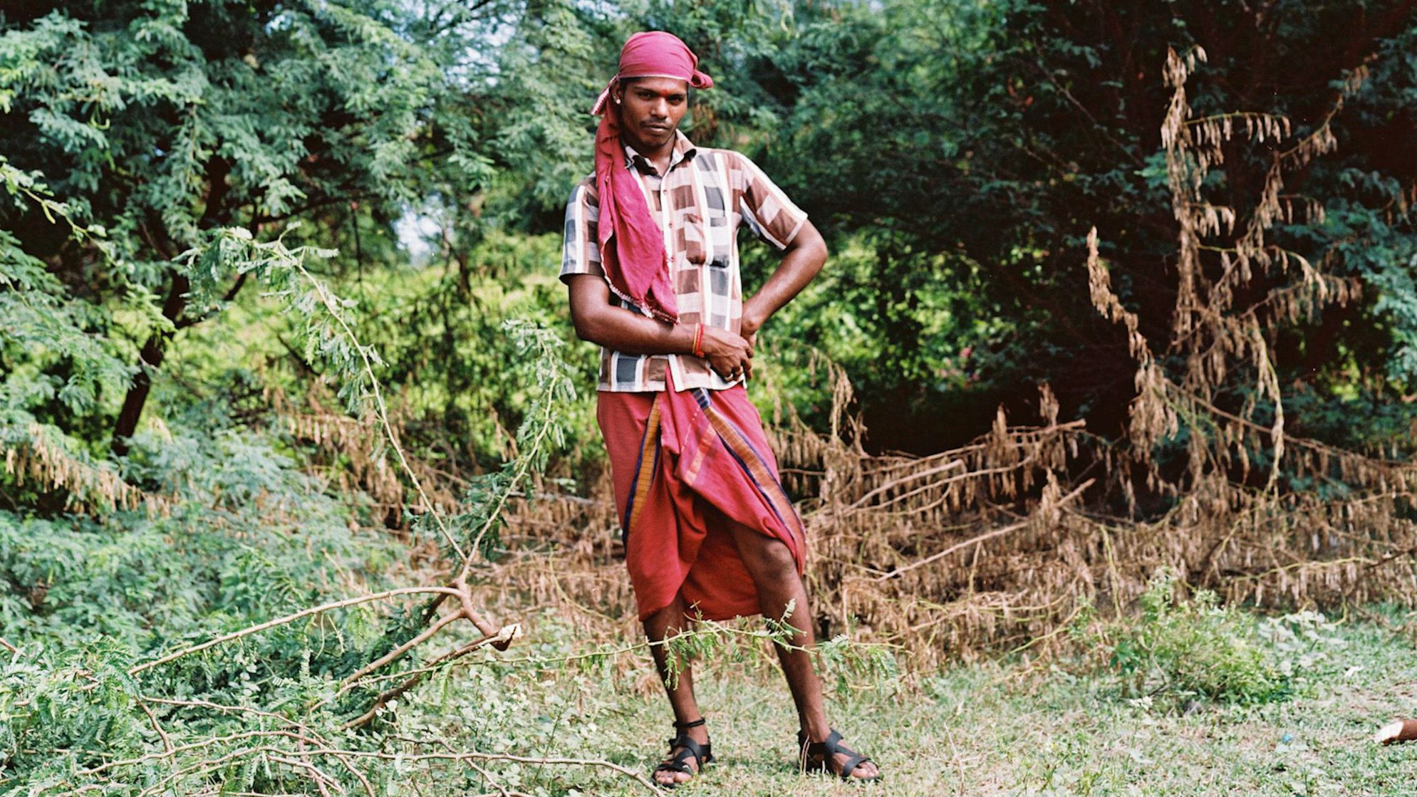 Chitra, a kothi priest from outside of Cuddalore, poses for a portrait while cutting down wood used for cooking. Many kothis choose to do this kind of work – which is tradi- tionally done by women – as another way to express their female identity. November 2013.