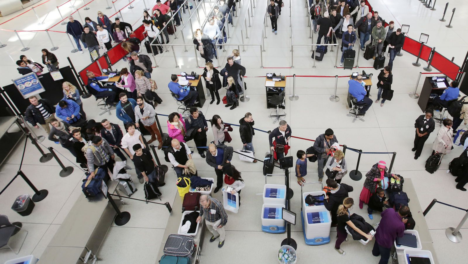 In this Oct. 30, 2014 photo, passengers line up to pass through security before boarding flights at John F. Kennedy International Airport in New York. A snowstorm is forecast for Wednesday and Thursday, Thanksgiving Day, for parts of the East Coast, potentially snarling holiday travel plans. (AP Photo/Mark Lennihan)
