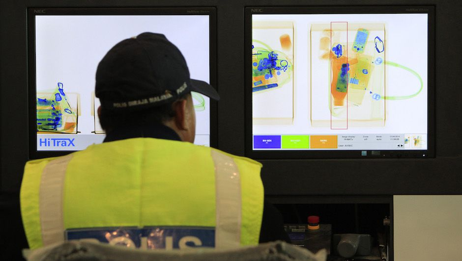 A Malaysian police officer monitors an X-ray machine during the Operational Readiness and Airport Transfer (ORAT) at the new budget airport KLIA2, in Sepang, Malaysia, Saturday, April 12, 2014. The KLIA2 will start operating on May 2. (AP Photo/Lai Seng Sin)