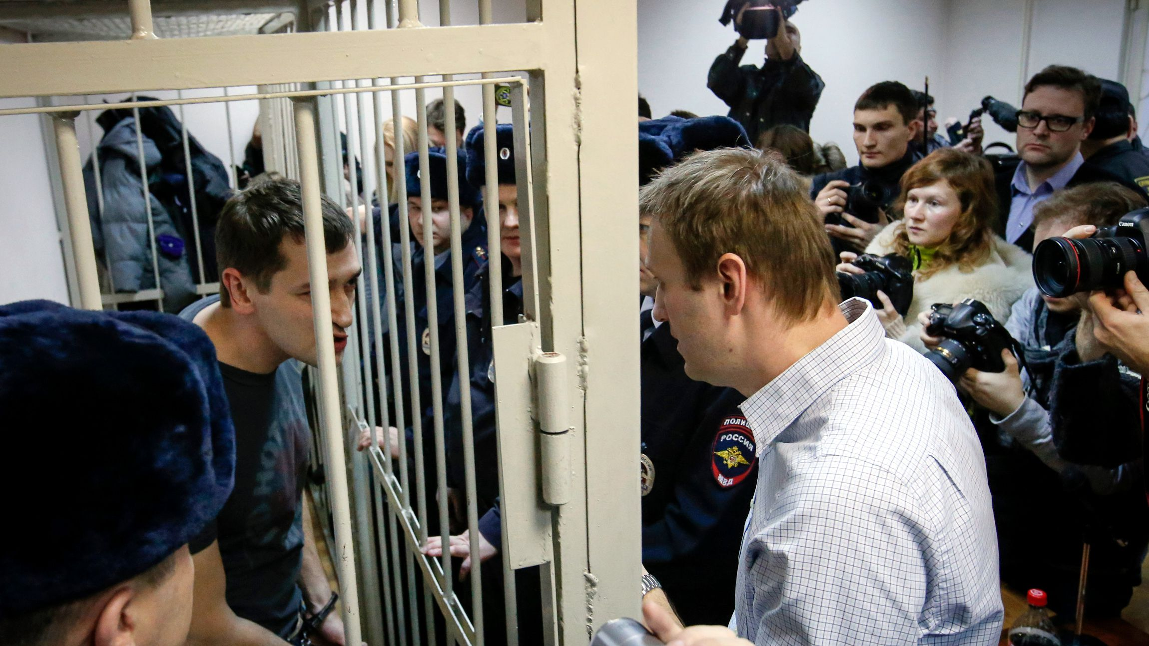 Russian opposition leader and anti-corruption blogger Alexei Navalny (R) talks with his brother and co-defendant Oleg (inside defendants cage) during a court hearing in Moscow December 30, 2014. A Russian court ruled on Tuesday to give Kremlin critic Alexei Navalny a suspended sentence for embezzling money but jailed his brother for three and a half years in a case seen as part of a campaign to stifle dissent.