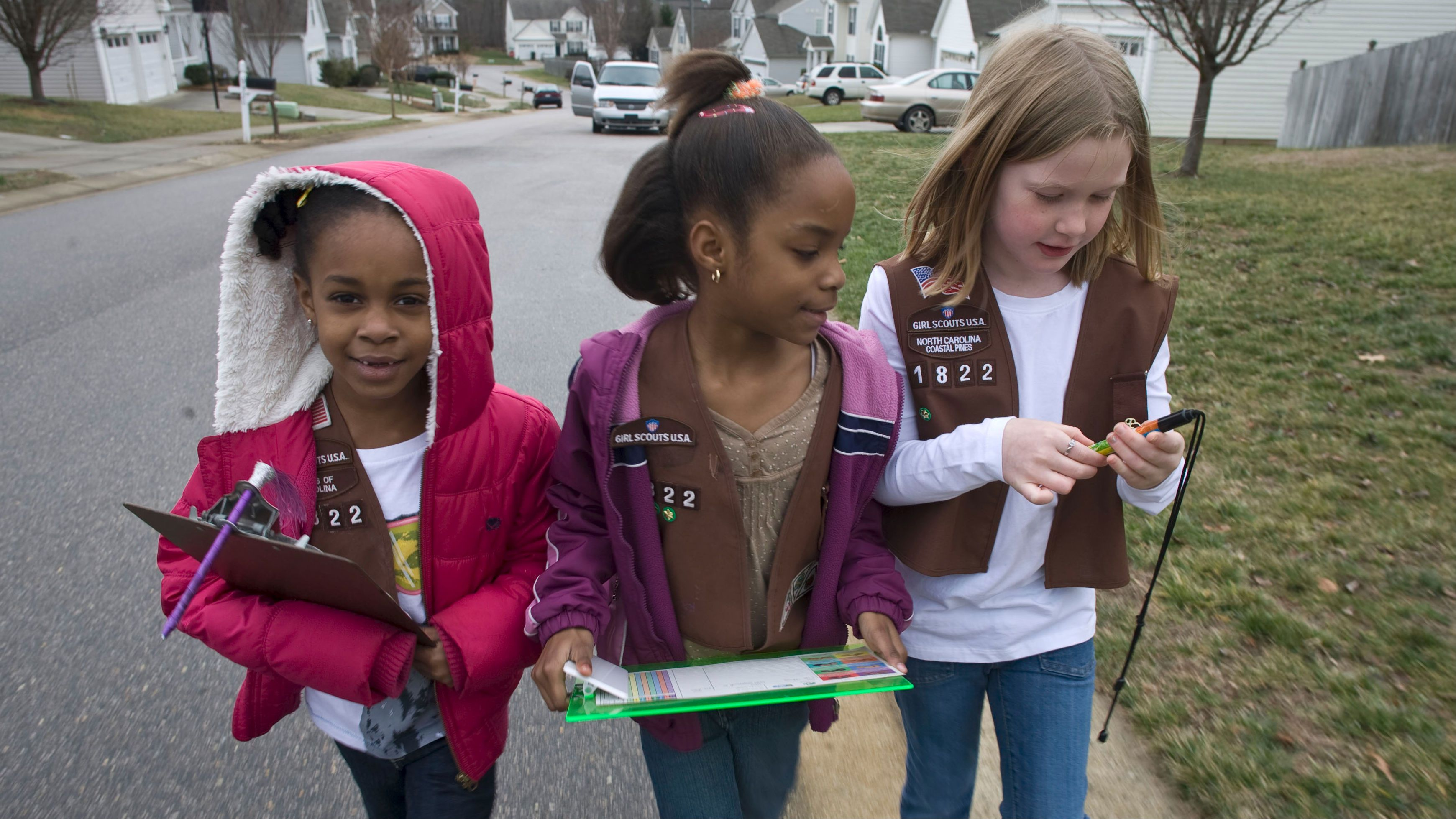 ** FOR RELEASE IN PMS EDITIONS OF WEDNESDAY, FEB. 4** Troop 1822 Brownie Scouts Aliya Gill, left, Lindsey Russ, center, and Natalie Rouse, canvass a north Raleigh neighborhood selling Girl Scout cookies on Saturday, Jan. 24, 2009. Ever the optimists, Girl Scouts have hit the ground running - and walking - knocking on door after door in the annual rite of selling their cookies. But this year some Scouts have bumped up against an intractable opponent: the economy. (AP Photo/The News & Observer, Robert Willett)