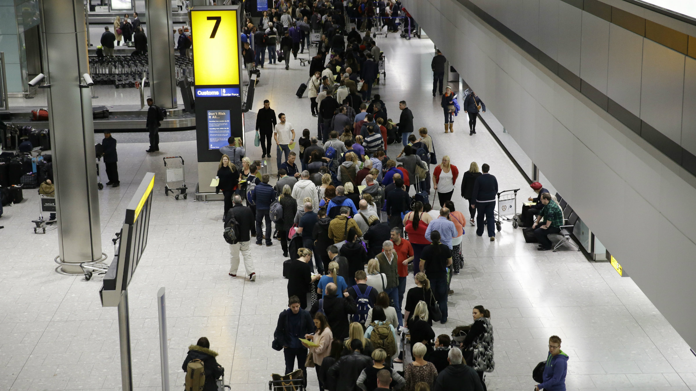 People queue in the luggage hall of Terminal 5 at Heathrow Airport in London, Friday, Dec. 12, 2014.