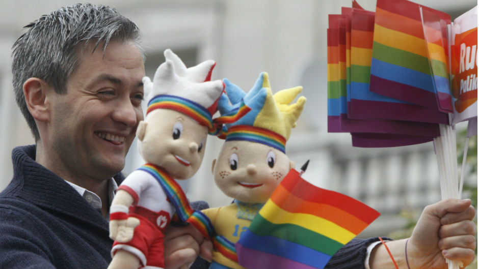 Lawmaker Robert Biedron holds Euro 2012 soccer championships mascots covered with a multicolor flag during the gay parade in Warsaw, Poland, Saturday, June 2, 2012.