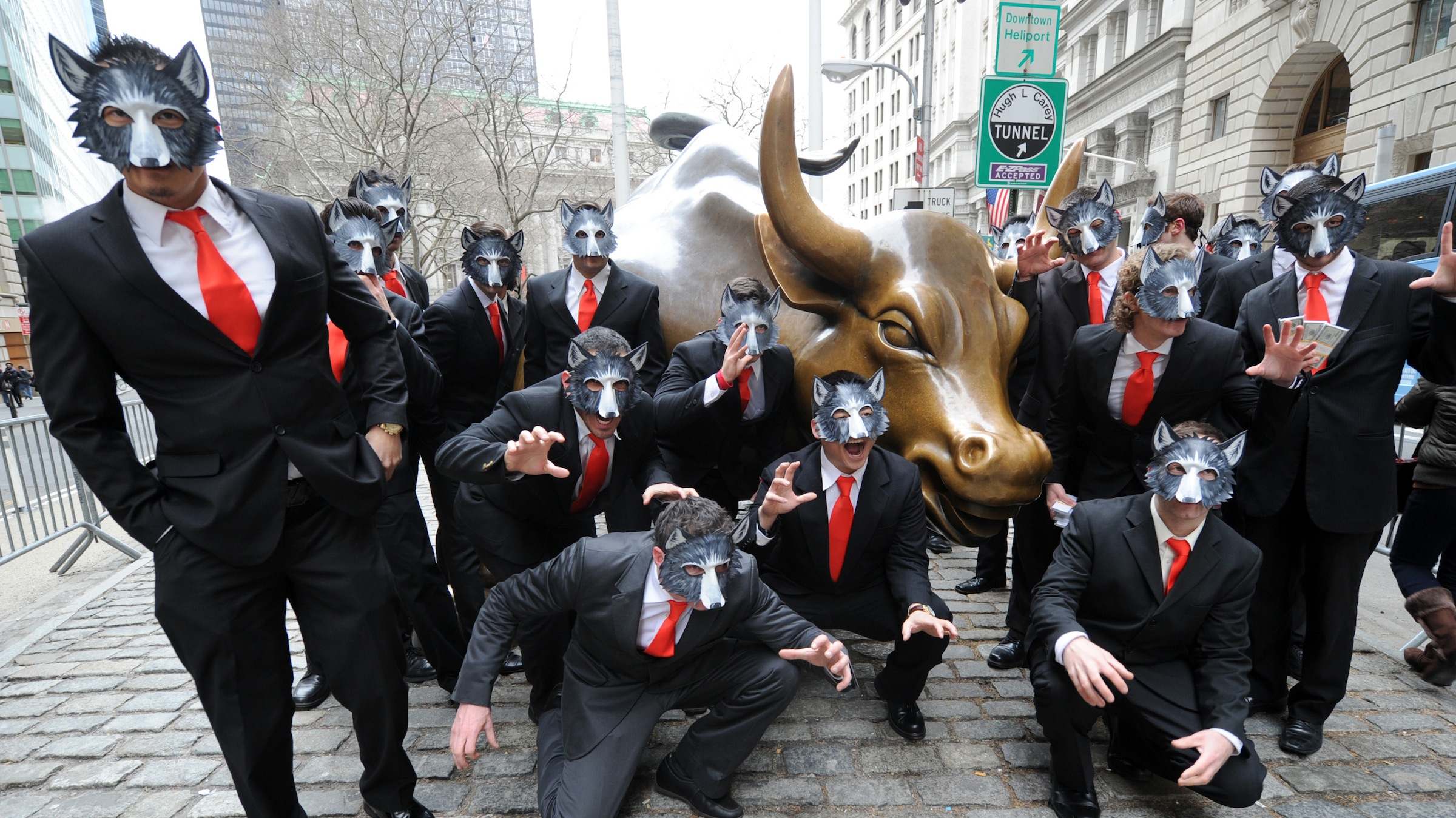 """IMAGE DISTRIBUTED FOR PARAMOUNT PICTURES - A pack of """"wolves"""" surround the Wall Street Bull, Tuesday, March 25, 2014, in New York, to celebrate the Blu-ray release of the hit movie The Wolf of Wall Street. (Photo by Diane Bondareff/Invision for Paramount Pictures/AP Images)"""