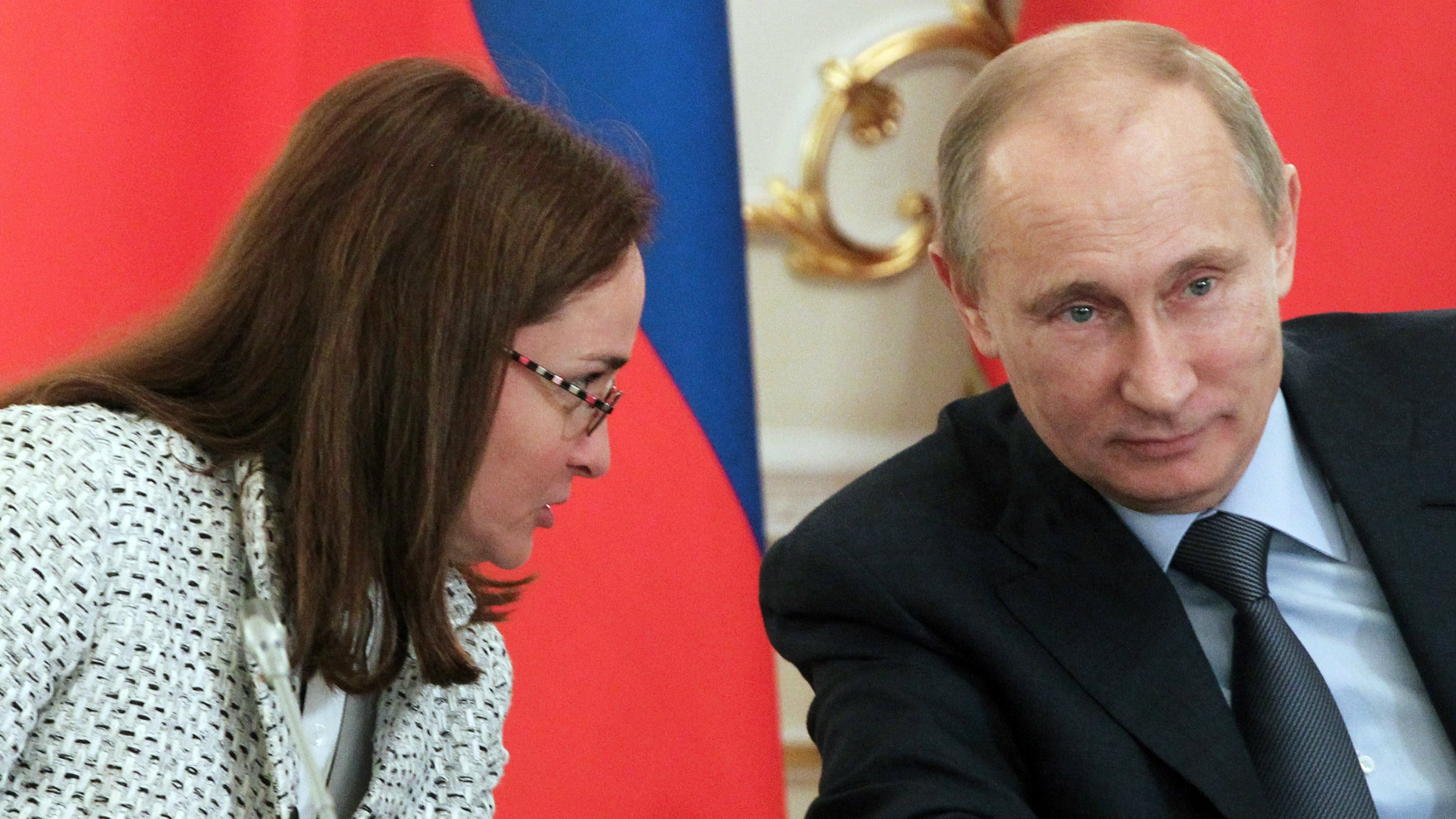 Russian President Vladimir Putin, right, listens to his aide Elvira Nabiullina