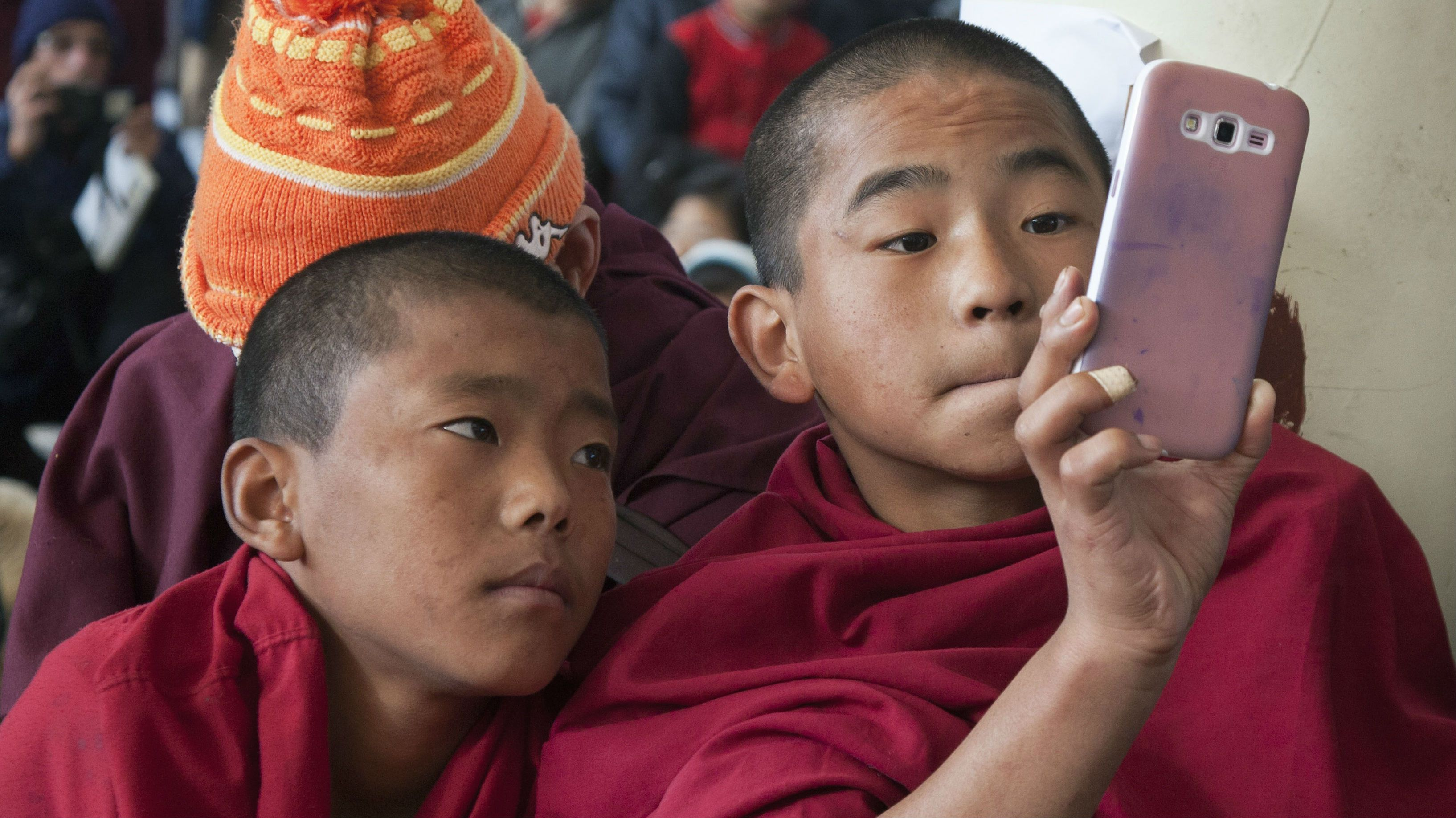 A novice exile Tibetan Buddhist monk uses his mobile phone camera as Tibetans gather to mark the 25th anniversary of their spiritual leader the Dalai Lama receiving the Nobel Peace Prize, at the Tsuglakhang temple in Dharmsala, Wednesday, Dec.10, 2014. The Tibetan leader was awarded the Peace Prize in 1989 for his commitment to non-violence. (AP Photo/Ashwini Bhatia)