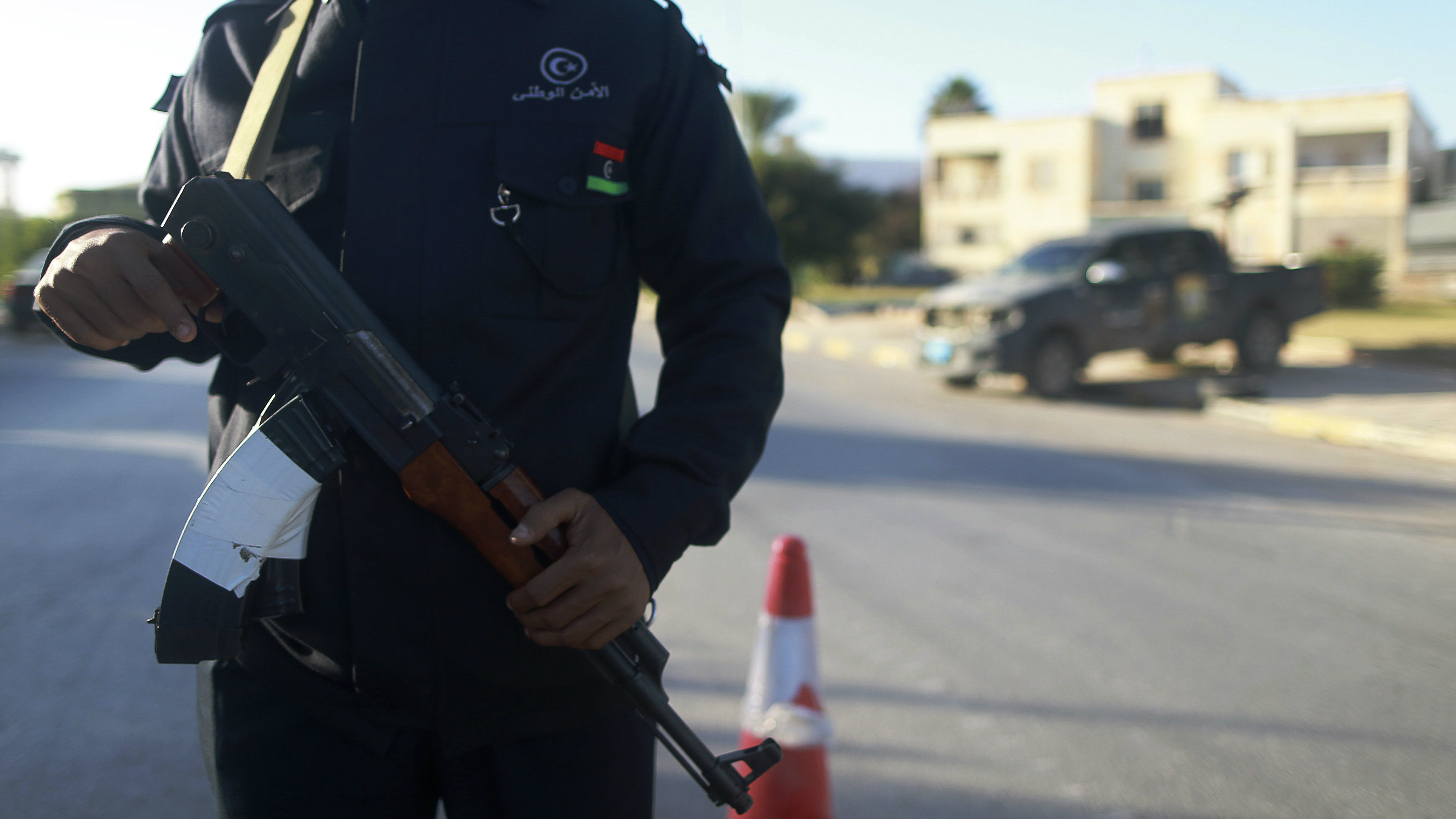 A security officer stands with his weapon on a road leading to a police station in Benghazi December 4, 2014. Police stations, prisons and the local security headquarters have reopened in Libya's eastern city of Benghazi for the first time in over a year, officials said, after pro-government forces seized back part of the port city.