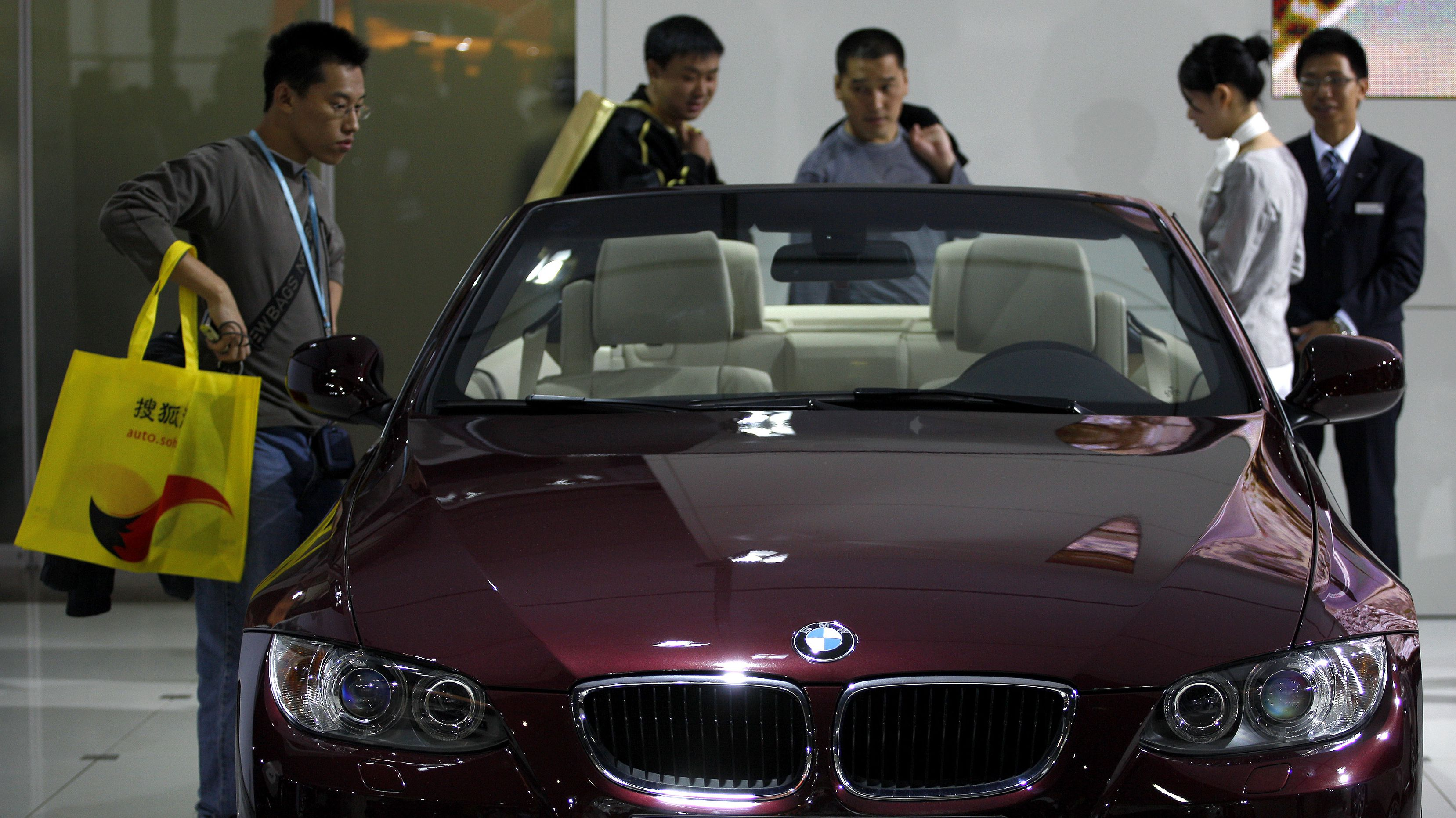 Visitors look at a BMW 320i convertible car at the Guangzhou Autoshow November 23, 2009. China's car makers hope Beijing will renew strong economic incentives that propelled China's car sales to record levels this year even in the face of the global downturn. REUTERS/Tyrone Siu