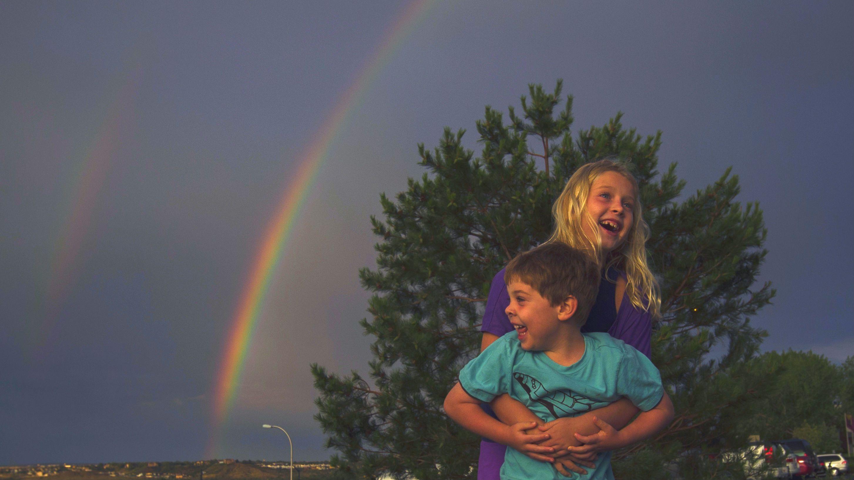 Children playing under a rainbow