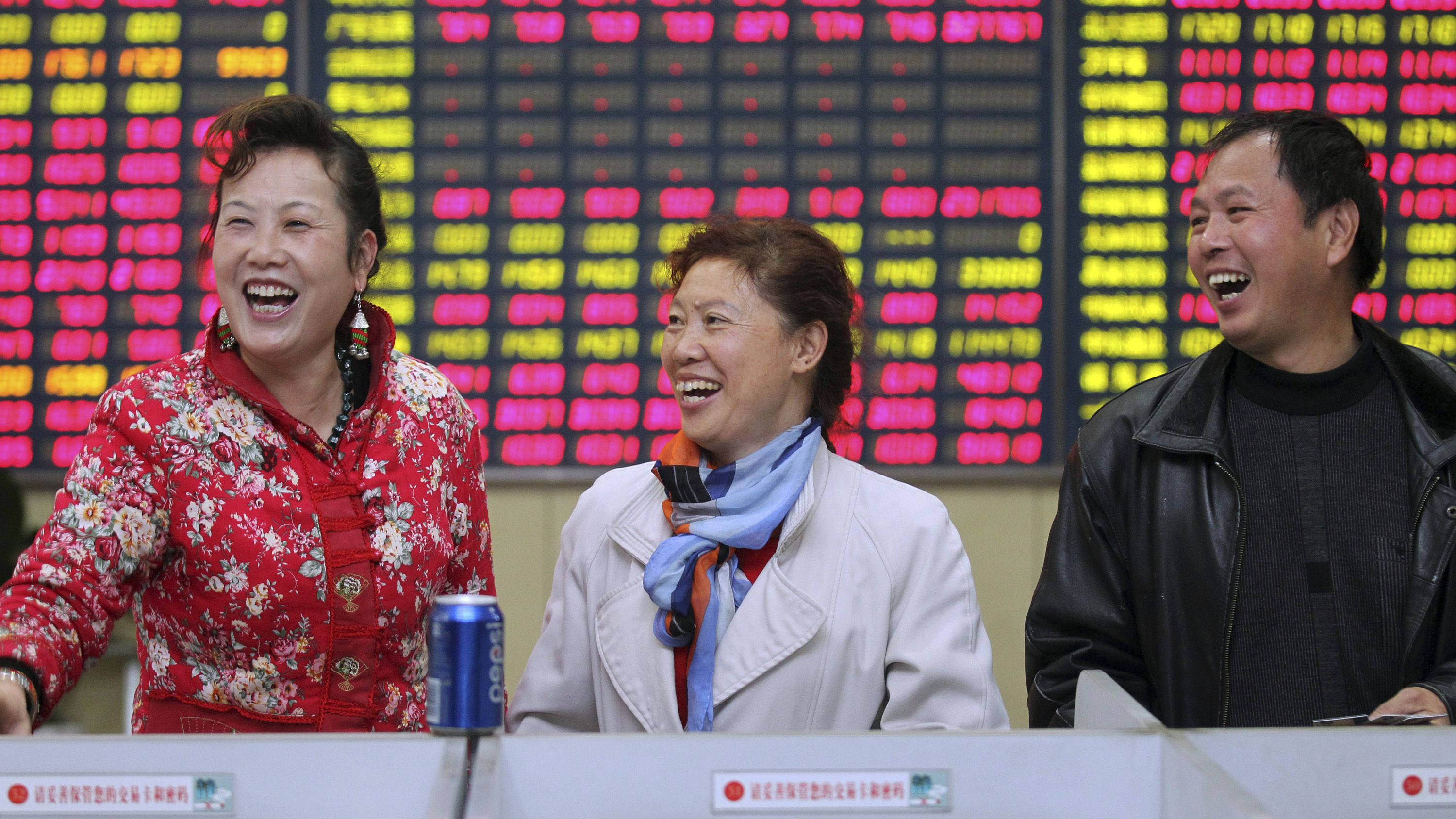 DATE IMPORTED:November 24, 2014Investors laugh in front of an electronic screen showing stock information at a brokerage house in Nantong, Jiangsu province, November 24, 2014. Chinese stocks rose, with a key index hitting a three-year high, while bond yields fell on Monday. REUTERS/China Daily