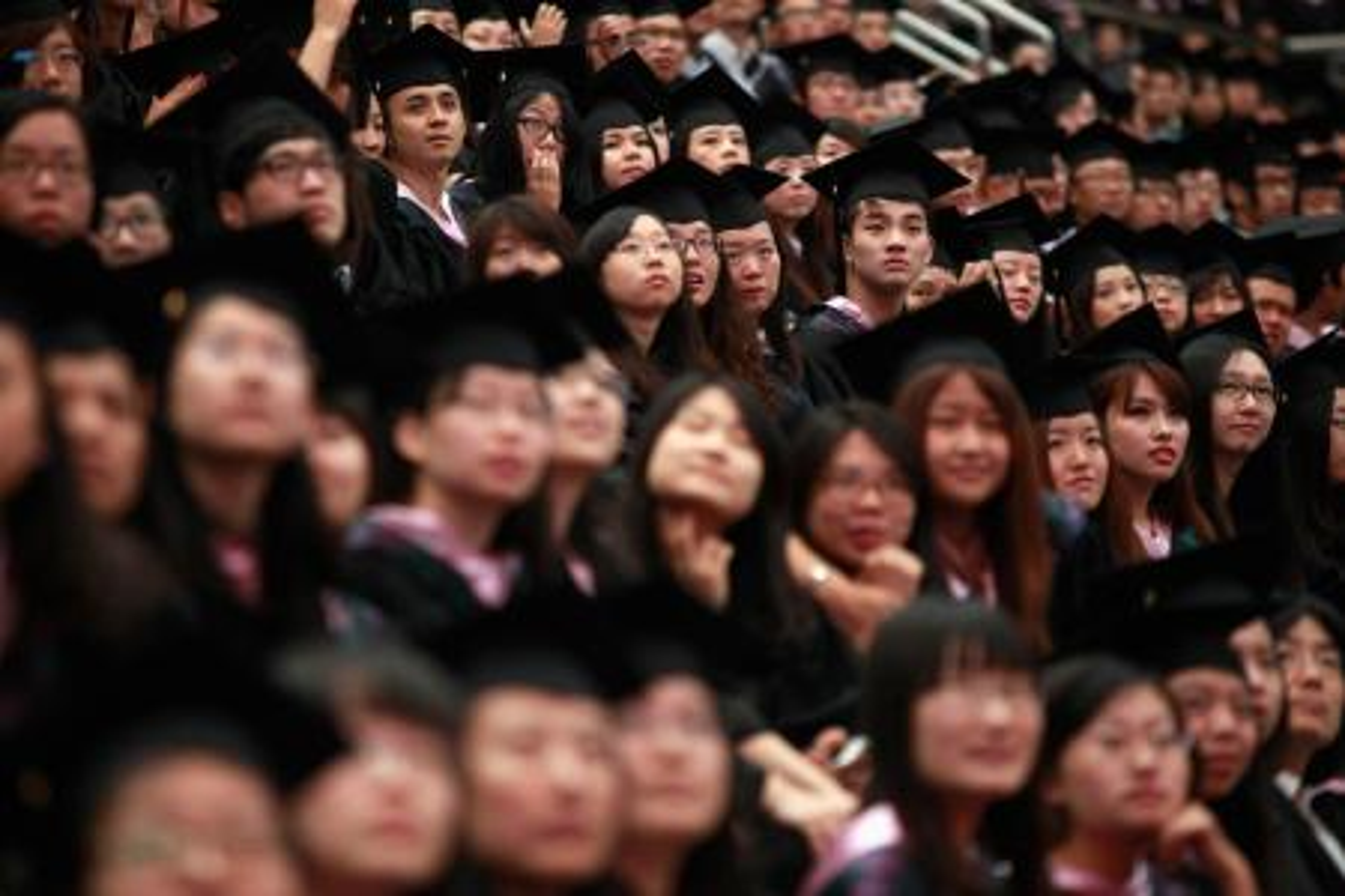 Graduates attend a graduation ceremony at Fudan University in Shanghai