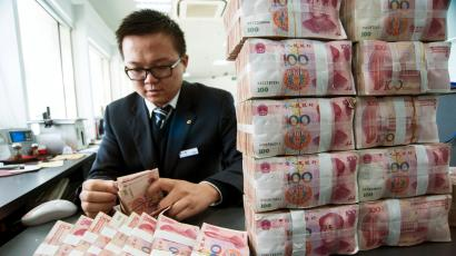 A clerk counts Chinese 100 yuan banknotes at a branch of China Construction Bank in Nantong, Jiangsu province December 2, 2014. China stocks leapt on Tuesday, as a mainland rally gained fresh steam, with investors pouring into brokerages and banking shares, widening the valuation gap with Hong Kong shares. Bank of China Ltd, Agricultural Bank of China Ltd and China Construction Bank Corp were all up close to 5 percent in late afternoon trading.