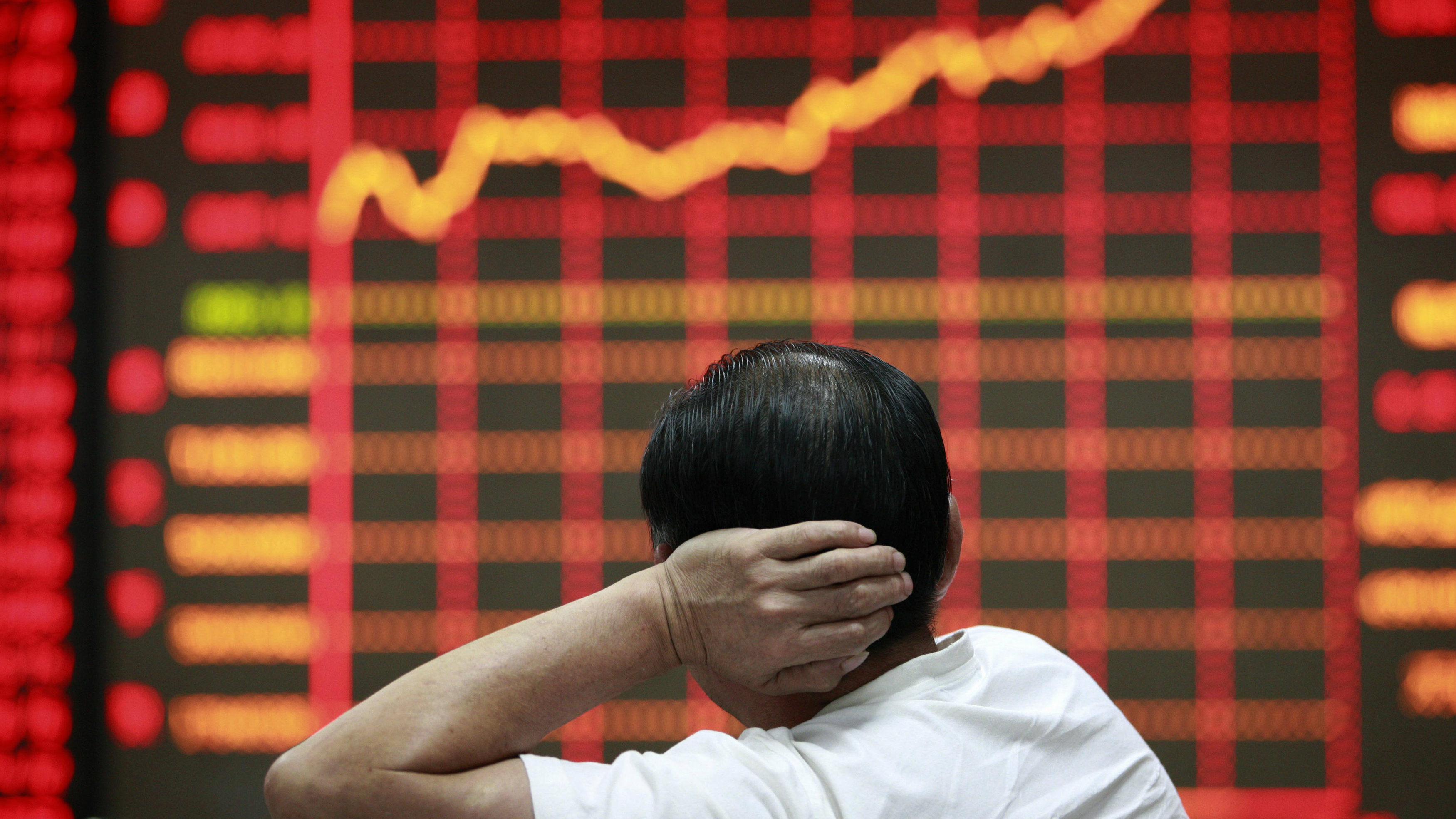 An investor looks at an electronic board showing stock information at a brokerage house in Huaibei, Anhui province.