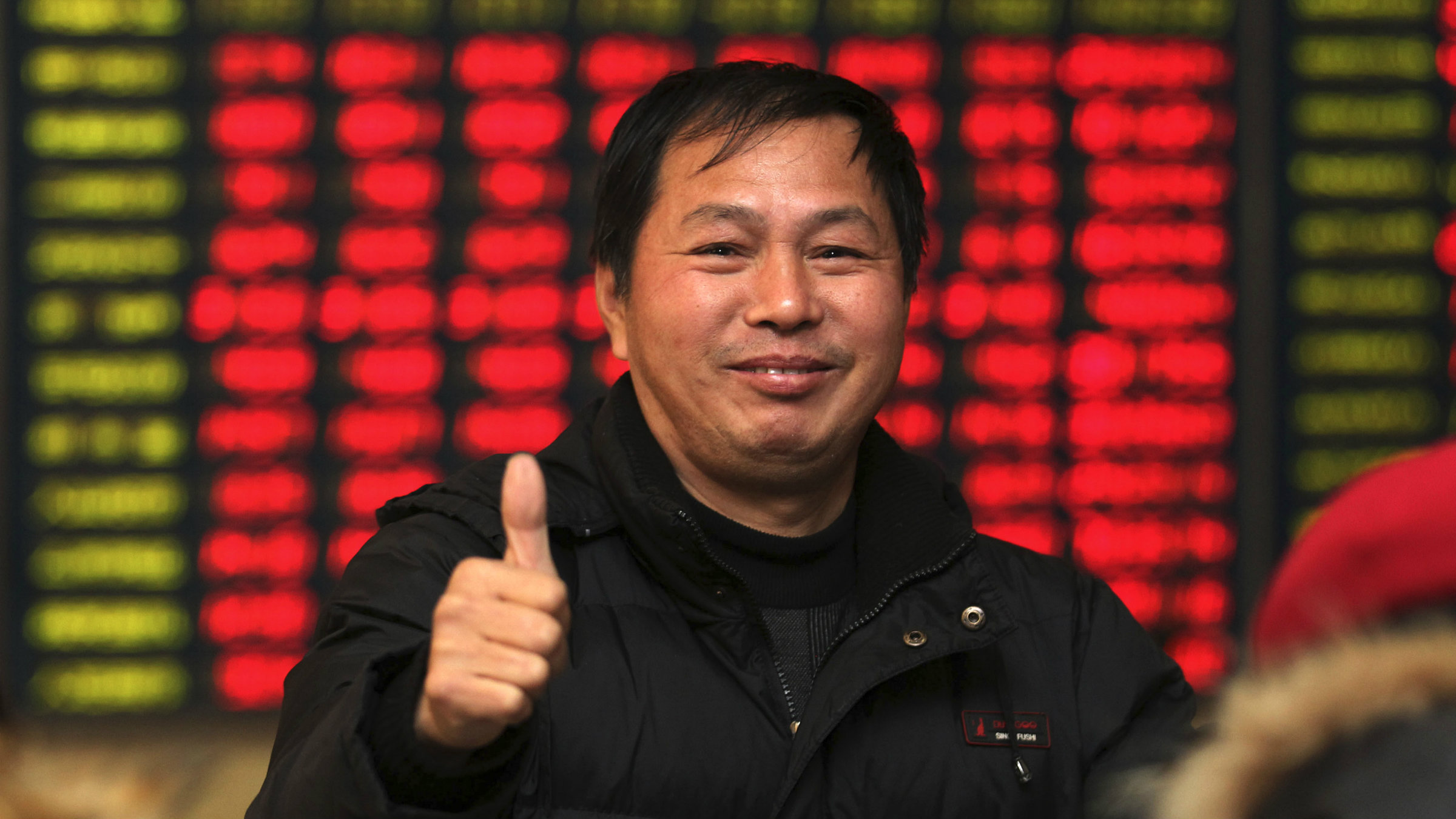 An investor gives a thumbs up as he talks to other investors in front of an electronic board showing stock information, filled with red figures indicating rising prices, at a brokerage house in Nantong, Jiangsu province.