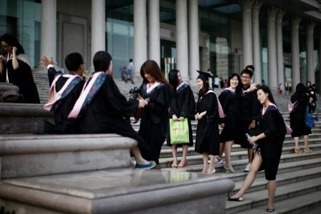 Graduates stand on the steps in front of the academic building at Fudan University in Shanghai.
