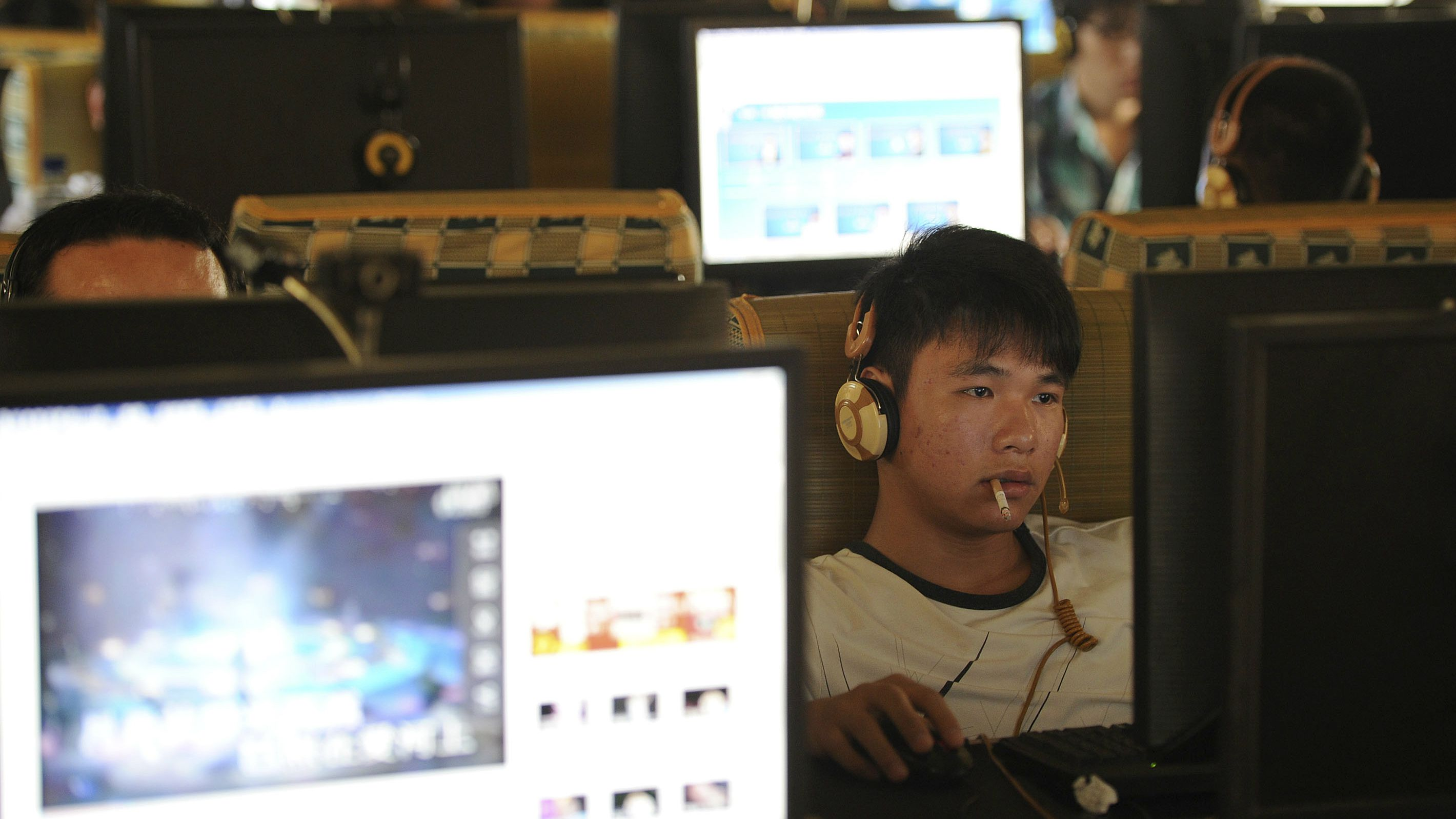 A man smokes as he uses a computer at an internet cafe in Hefei, Anhui province, September 15, 2011.