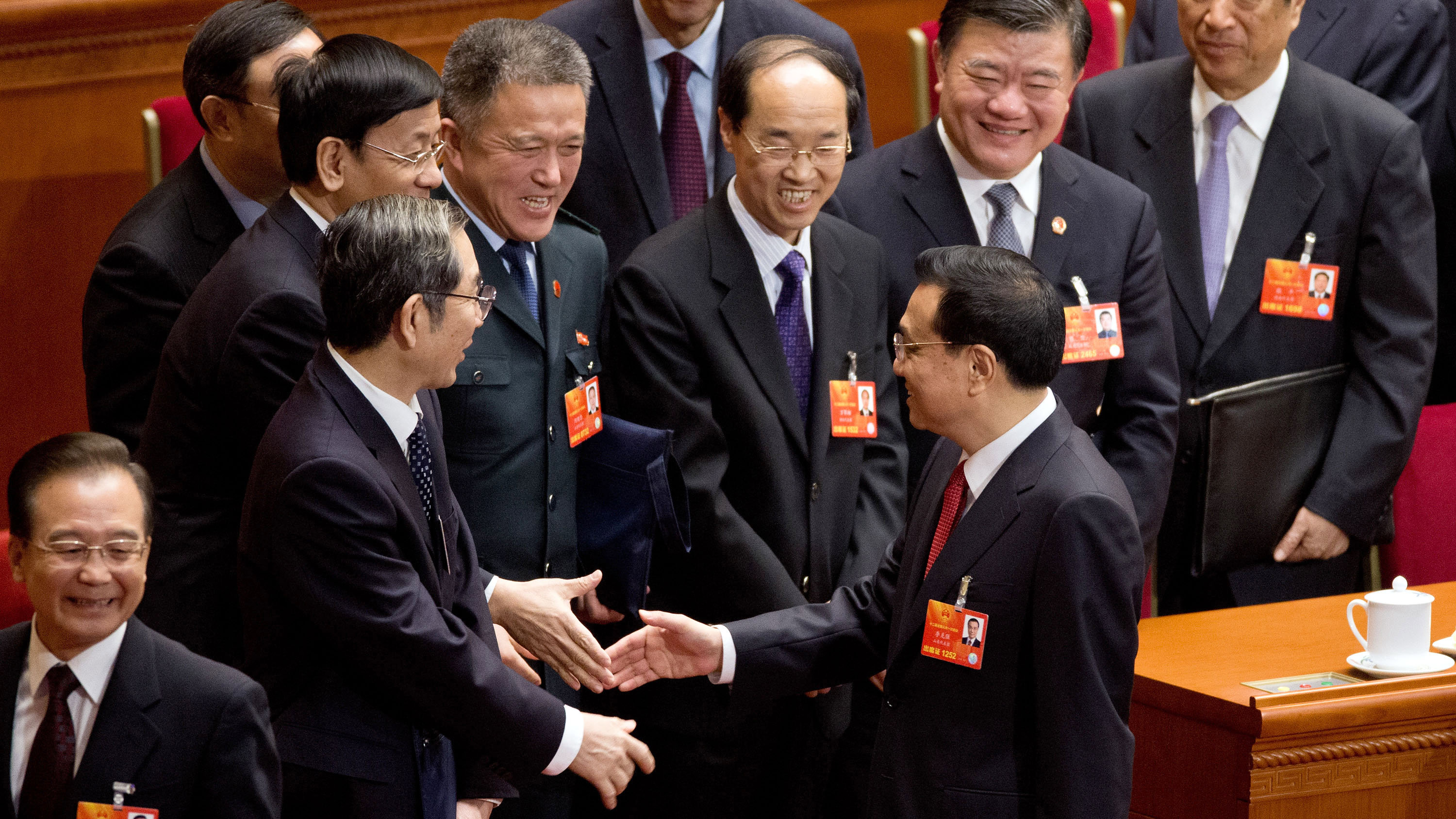 New Chinese Premier Li Keqiang, center, is greeted by delegates while his predecessor Wen Jiabao, left, walks away after a plenary session of the National People's Congress at the Great Hall of the People in Beijing Friday, March 15, 2013. China named the Communist Party's No. 2 leader, Li, premier on Friday as a long-orchestrated leadership transition nears its end, leaving the new leaders to confront uneven economic growth, unbridled corruption and a severely befouled environment that are stirring public discontent.
