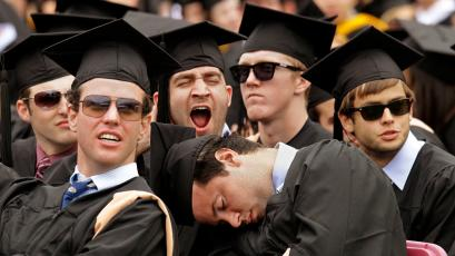 John Fiorenzo, center, catches a brief nap during the address to the graduates at his Boston College Commencement ceremony while a classmate yawns behind him at Alumni Stadium on the university's campus in Boston, Monday, May 21, 2012. Fellow graduates Patrick Dingham, left, and Brandan Kirby, right, watch the stadium's score board jumbotron. All of the men received their Bachelors of Science degrees from the university's Carrol School of Management. (AP Photo/Stephan Savoia)