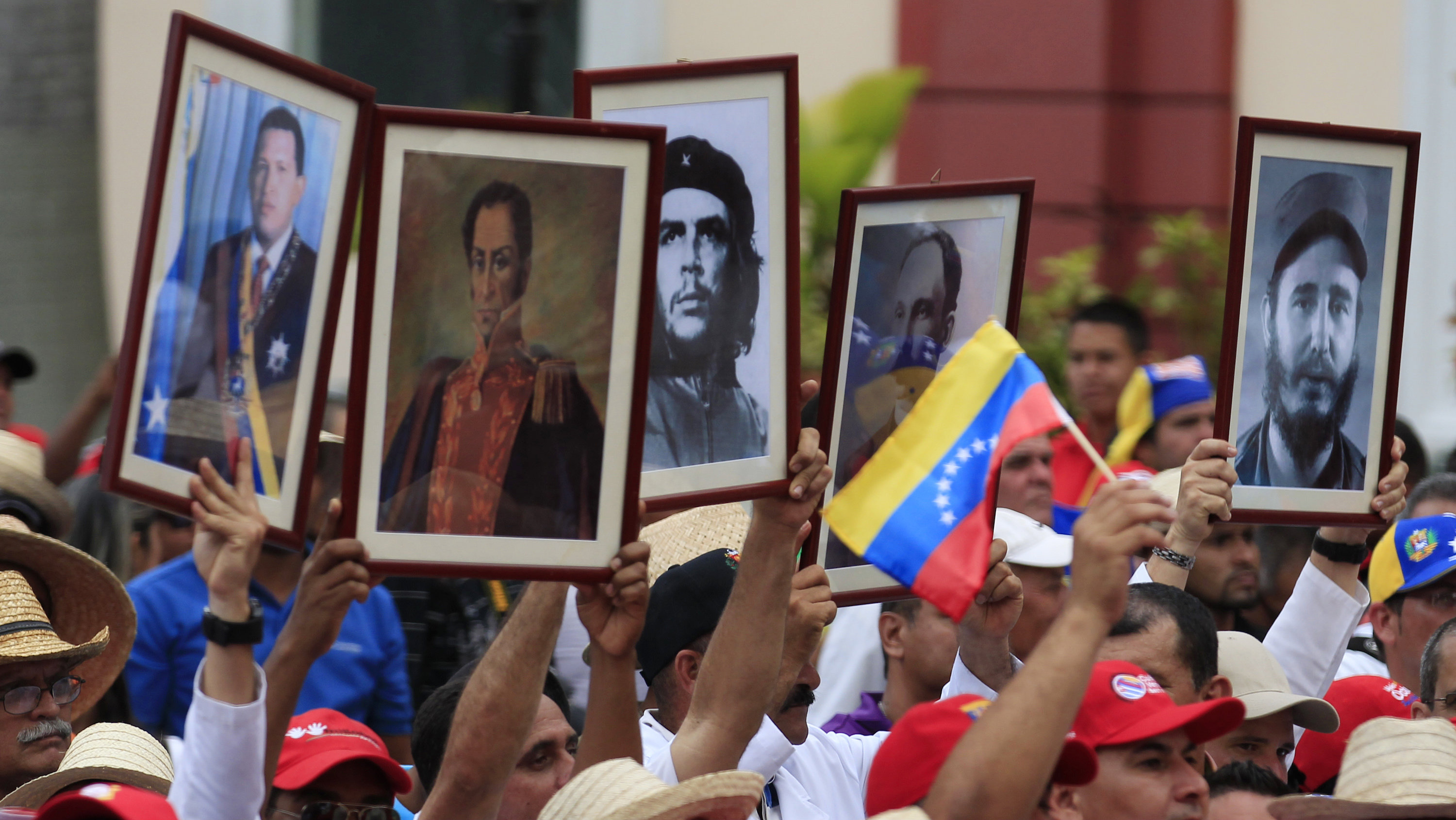 Cuban doctors hold up framed pictures (L-R) of late President Hugo Chavez, Venezuela's National hero Simon Bolivar, Ernesto 'Che' Guevara, Cuban national hero Jose Marti and Fidel Castro during a march of farmers in support of Venezuela's President Nicolas Maduro in Caracas February 26, 2014. Pope Francis called on Wednesday for an end to violence in Venezuela that has killed at least 13 people and urged politicians to take the lead in calming the nation's worst unrest for a decade. Both political camps were demonstrating in cities around the country. In the capital Caracas, female opposition supporters rallied while agricultural workers marched to the presidential palace in support of the socialist government.