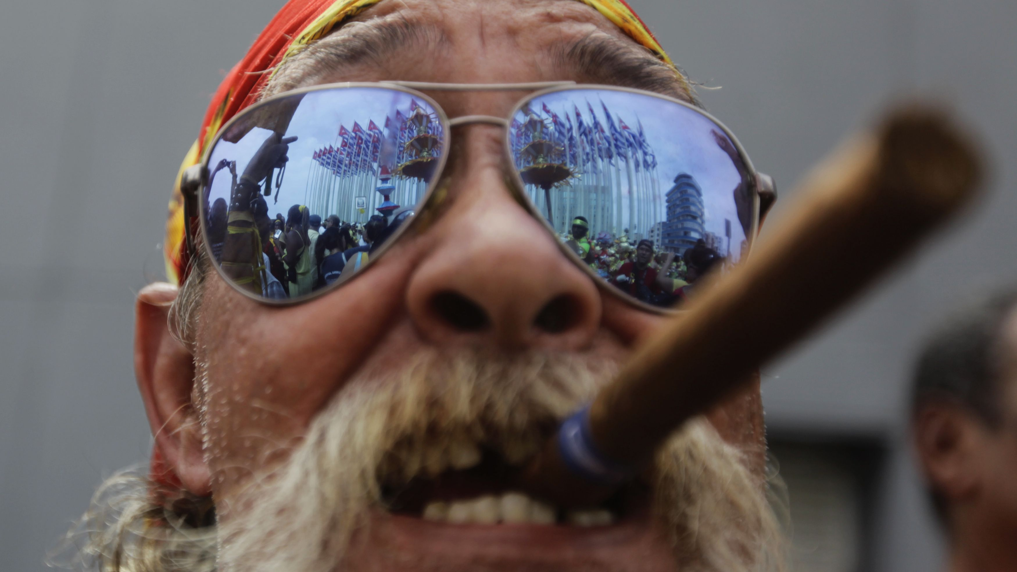 """A man holds a cigar in his mouth during a gathering beside the U.S. Interests Section diplomatic mission in Havana, September 12, 2013. Cuba held a day of protest on Thursday over four intelligence agents imprisoned in the United States, displaying yellow ribbons to show national support for bringing the men home on the 15th anniversary of their arrest in Florida. The men were convicted in 2001 of conspiring to spy on Cuban exile groups and U.S. military activities as part of an espionage ring called the """"Wasp Network."""" REUTERS/Desmond Boylan (CUBA - Tags: POLITICS) - RTX13J1K"""