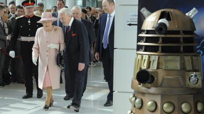 Britain's Queen Elizabeth II walks past a Dalek from the Doctor Who television series during a visit to the BBC's new buildings MediaCity in Salford, Greater Manchester, England, Friday March 23, 2012. The Queen and the Duke of Edinburgh visited Manchester and officially opened hospitals, toured the new BBC building and officially started a Sport Relief Mile fun run. (AP Photo/Andrew Yates, Pool)