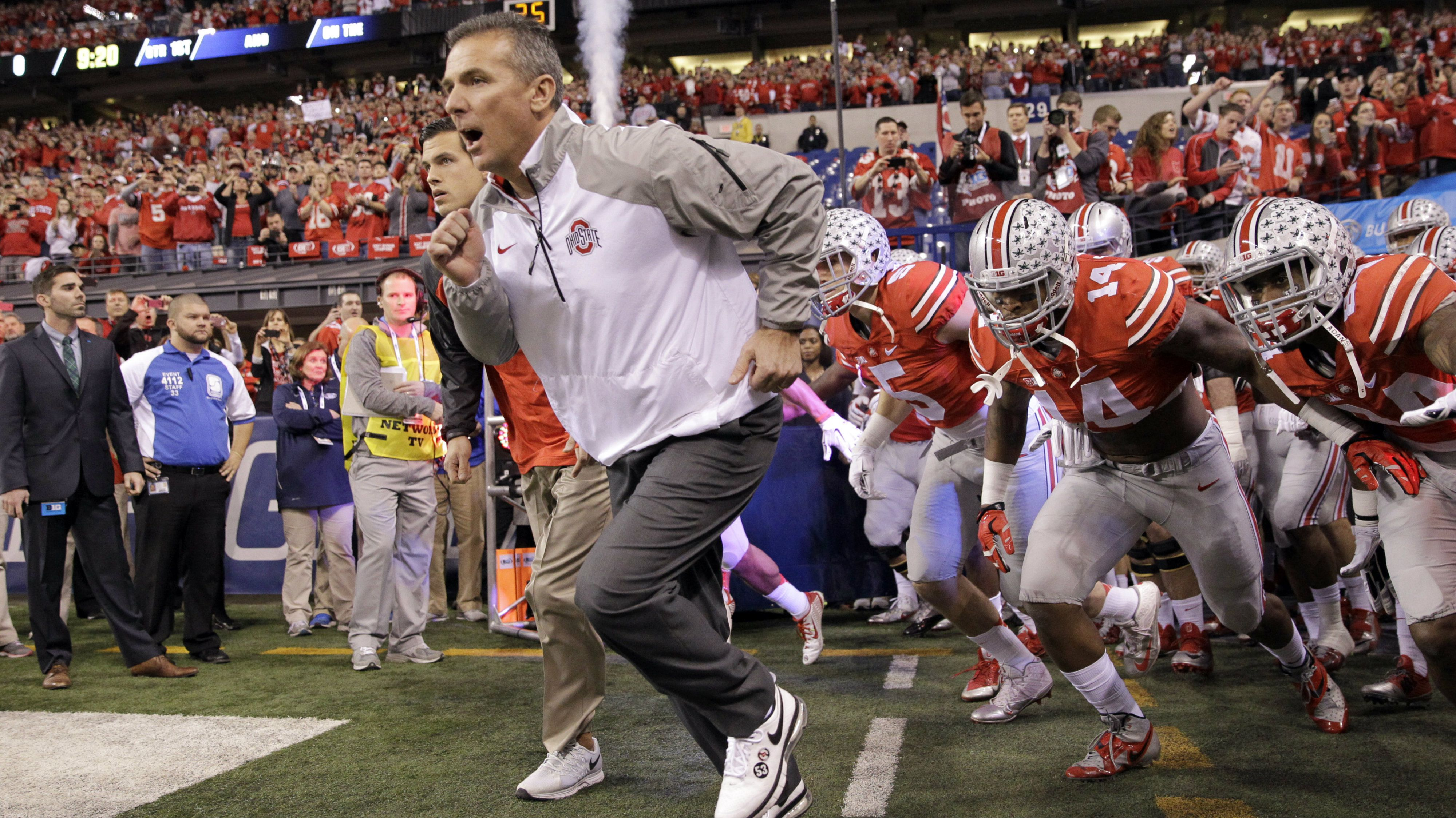 Ohio State head coach Urban Meyer runs onto the field with his team