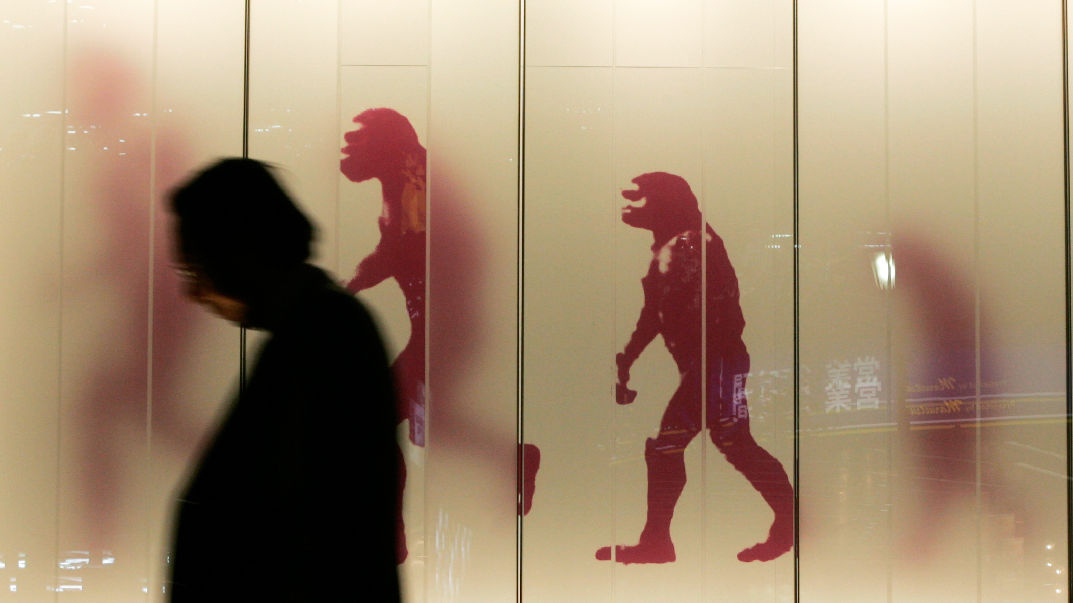 A man walks past a sign showing the evolution of man in a business district in downtown Tokyo November 17, 2008.