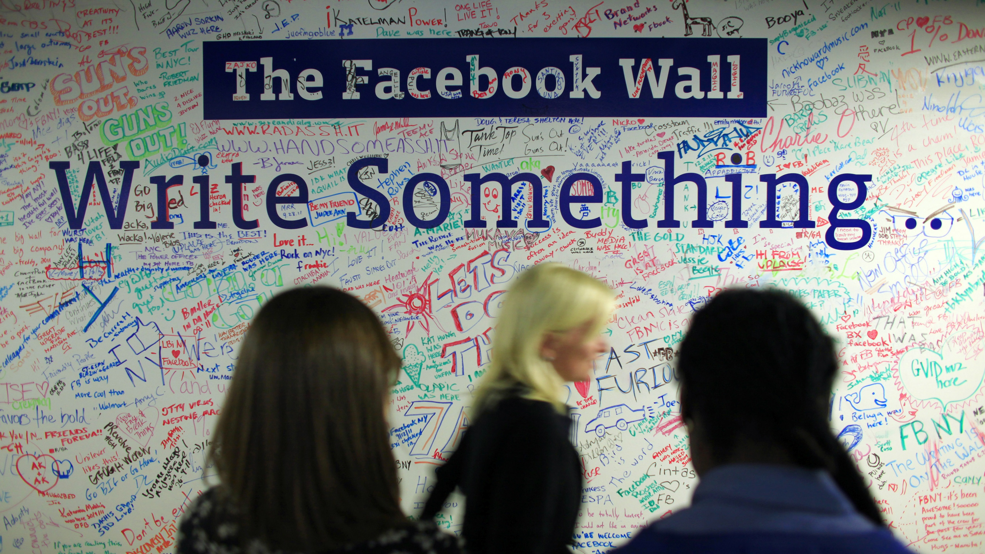 People walk past the Facebook wall inside their office in New York December 2, 2011. REUTERS/Eduardo Munoz (UNITED STATES - Tags: BUSINESS TPX IMAGES OF THE DAY)