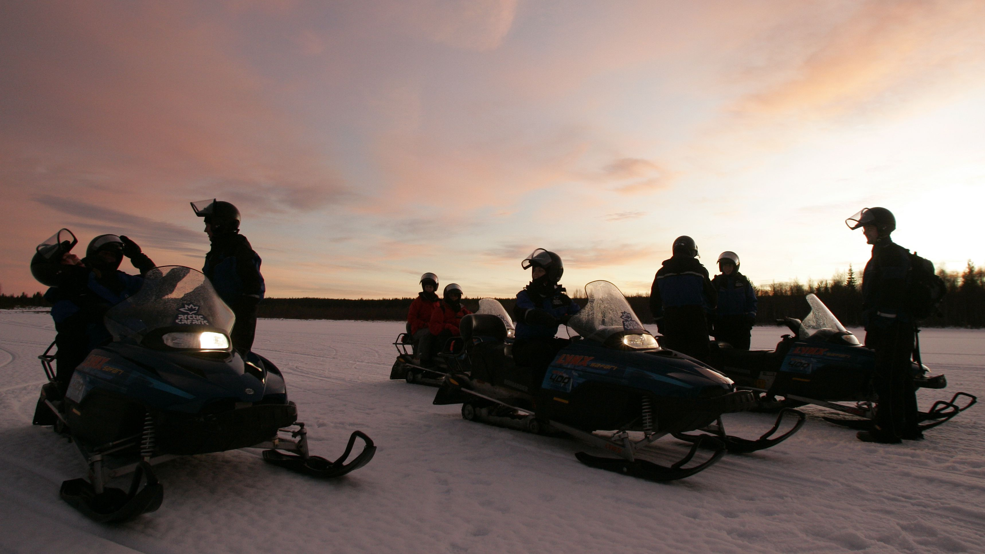 Tourists take a break from driving their snowmobile during an arctic safari at Arctic Circle near Rovaniemi, northern Finland, December 17,2007. REUTERS/Kacper Pempel