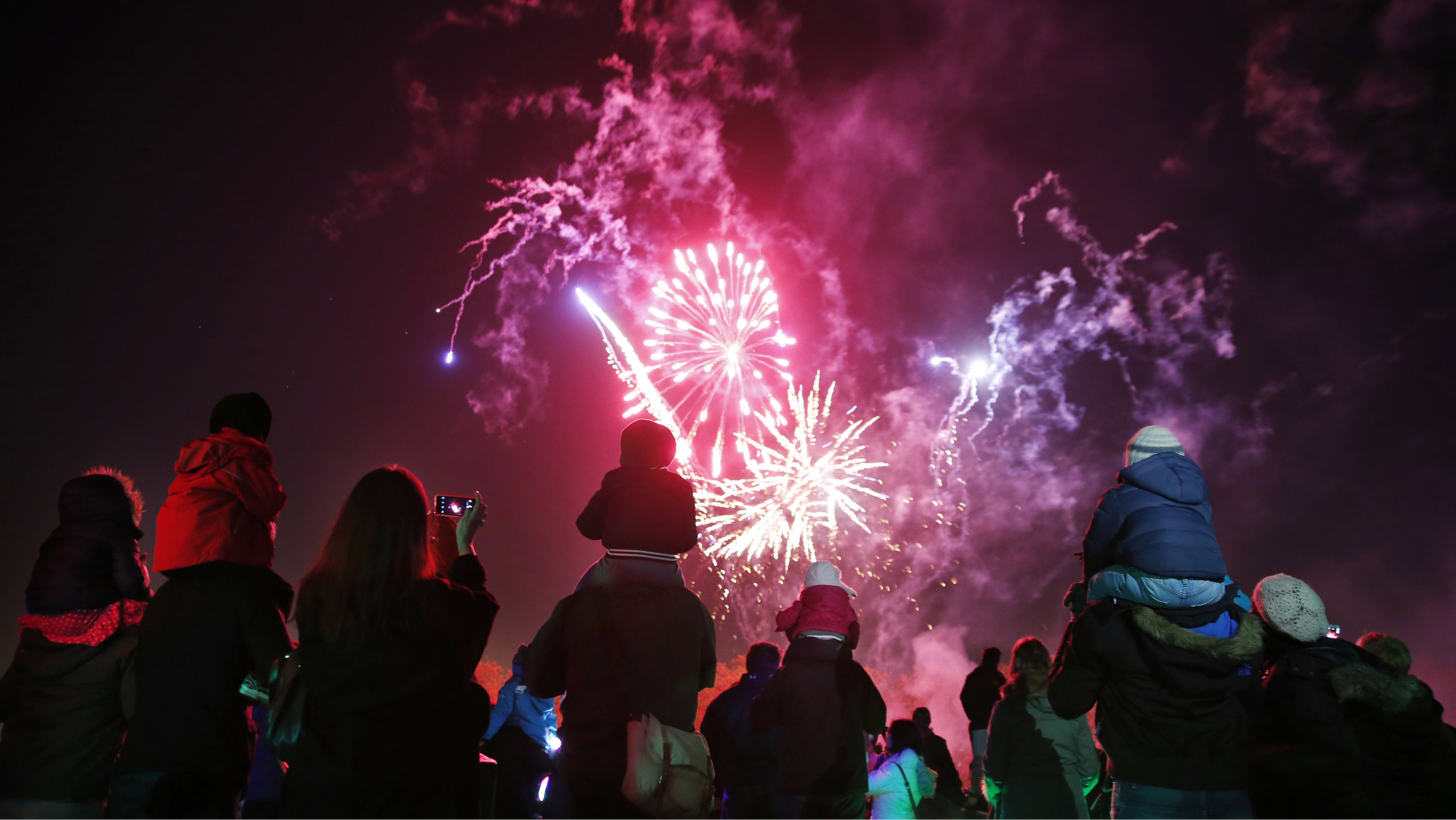 """Children sit on their parents' shoulders as they watch a bonfire night firework display at Roundwood Park in northwest London November 5, 2014. The fireworks display is one of many across the country which marks the uncovering of Guy Fawkes' """"Gunpowder Plot"""" to blow up the Houses of Parliament in 1605."""