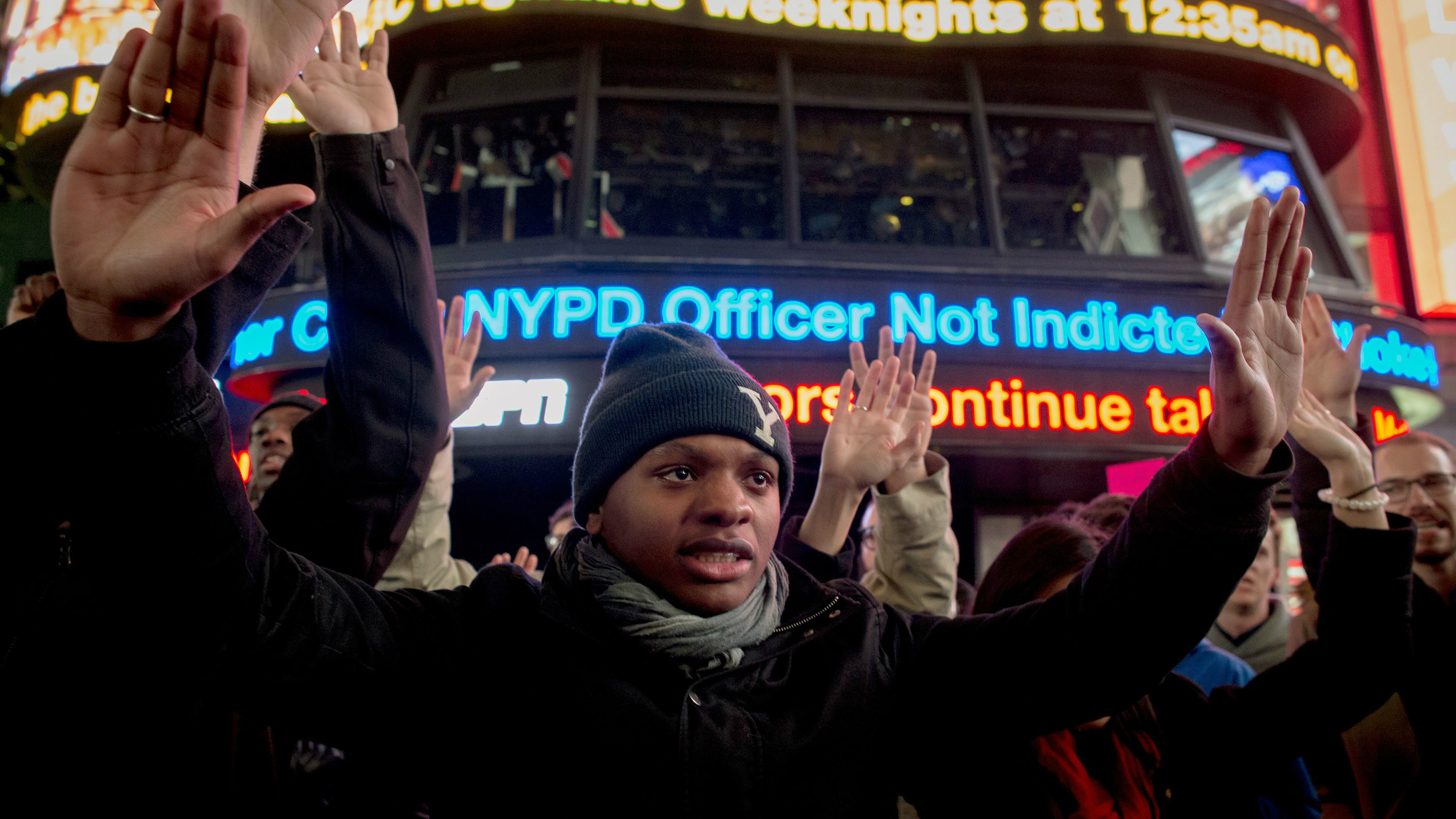 Demonstrators hold their hands up during a protest against the grand jury decision in the Eric Garner case, in Times Square in New York December 3, 2014.