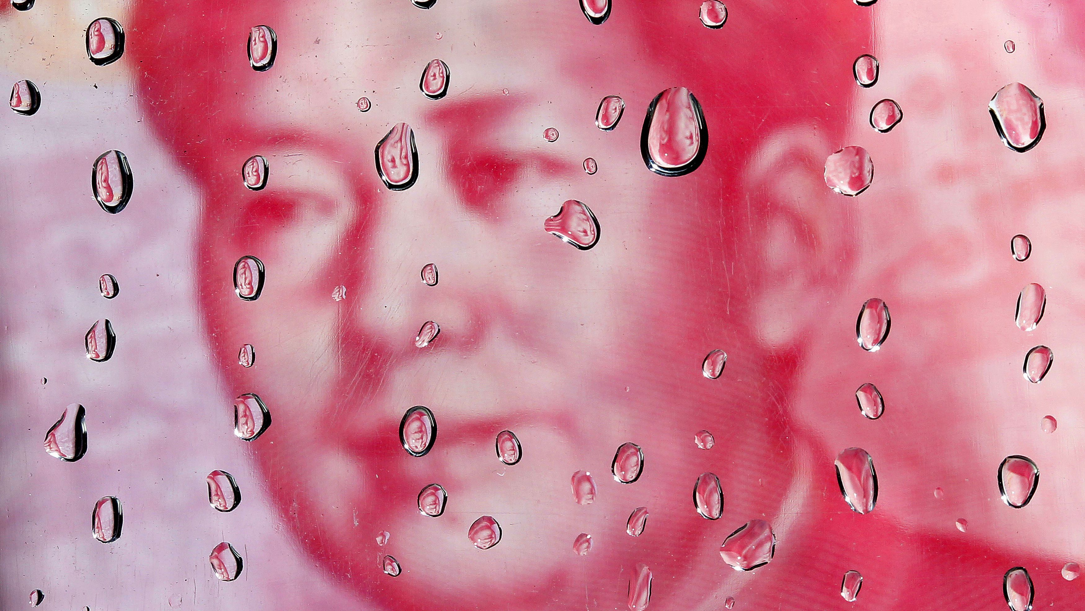 DATE IMPORTED:October 08, 2010A portrait of former Chinese leader Mao Zedong on a yuan banknote is reflected in water droplets in this picture illustration taken in Taipei October 8, 2010. REUTERS/Nicky Loh