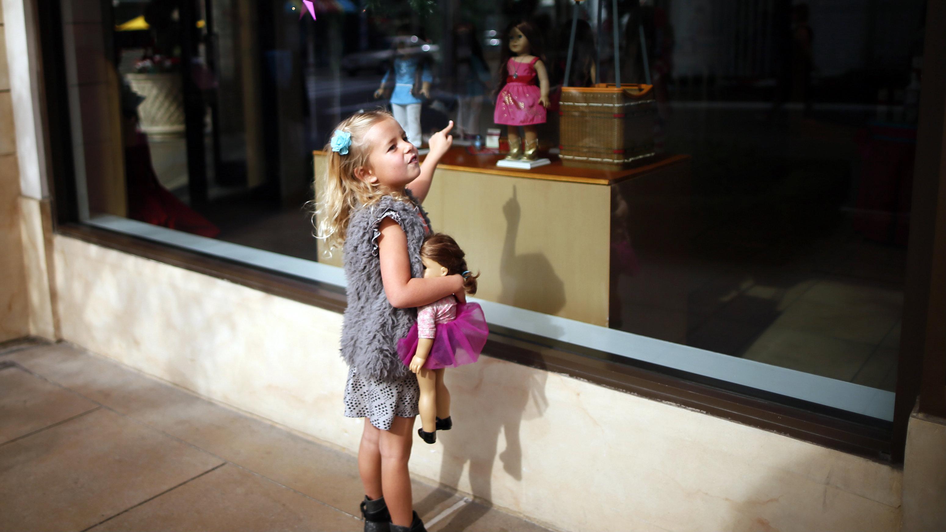 Girl pointing at doll