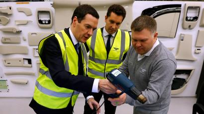 Britain's Chancellor of the Exchequer George Osborne (L) talks to a worker in the trim facility at Bentley Motors in Crewe, northern England December 4, 2014.