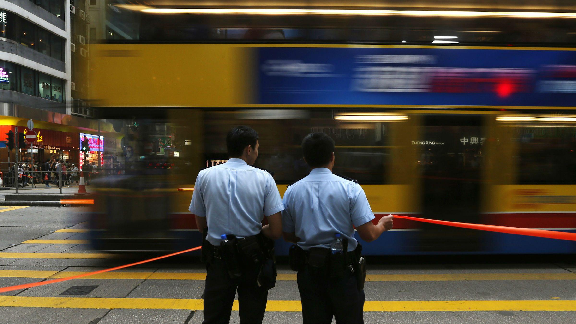 A bus drives past two policemen at the main Nathan Road after normal traffic resumed, at Mongkok shopping district in Hong Kong November 26, 2014