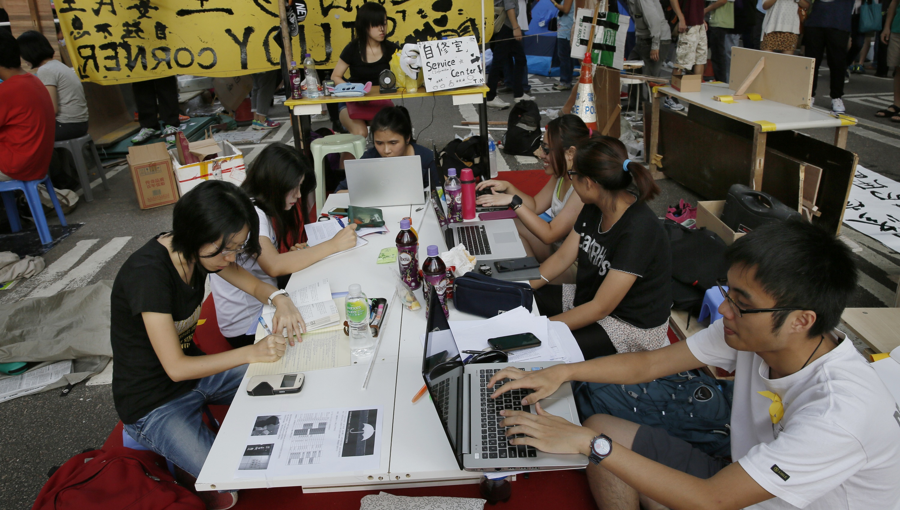 Pro-democracy students do their homework at a study area at a main road in the occupied areas in Hong Kong's Admiralty district, Saturday, Oct. 11, 2014. Students and activists demanding a greater say in choosing the city's leader have vowed to stay until the government responds, while the government has repeatedly urged protesters to withdraw from the streets and allow the city to return to normal. (AP Photo/Vincent Yu)