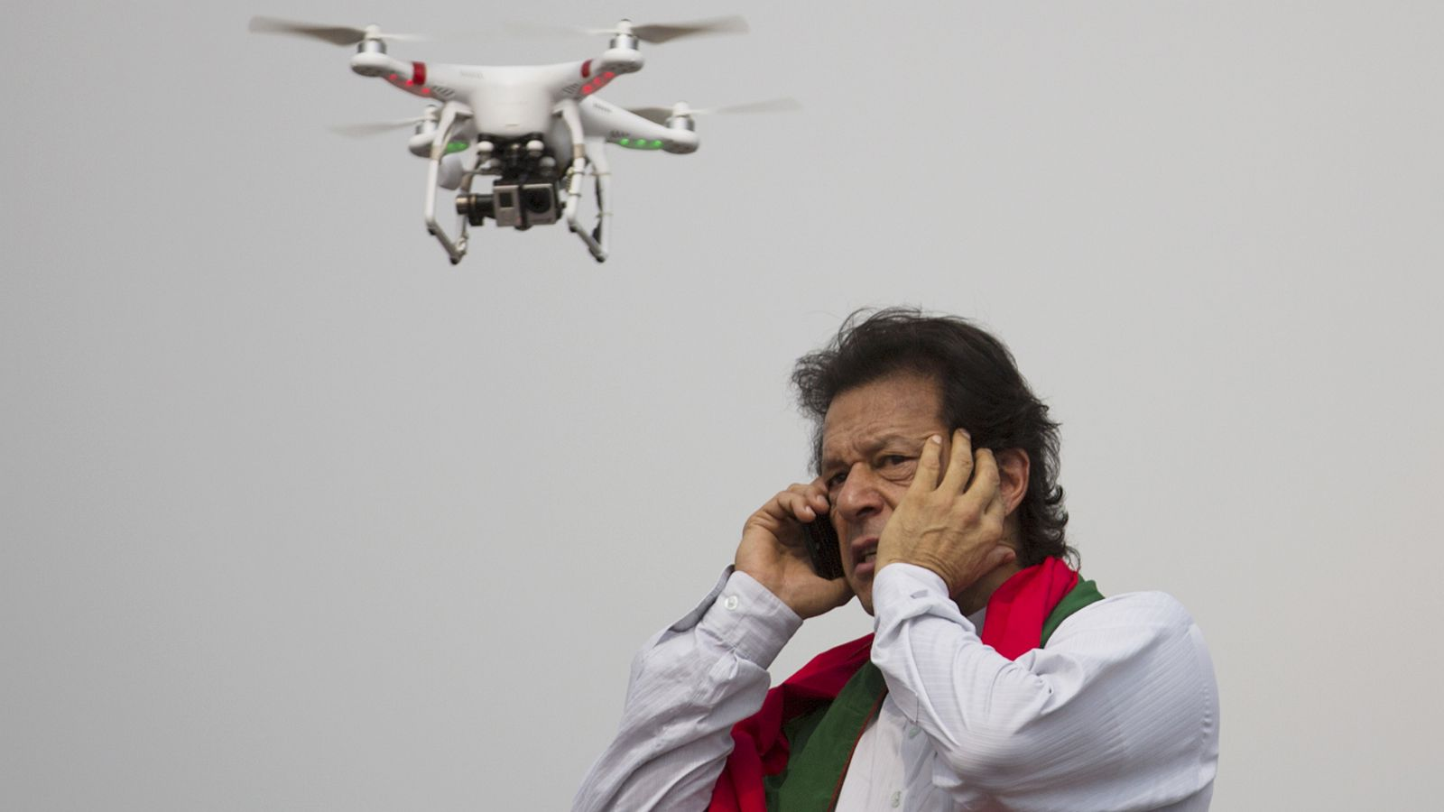 Pakistan's cricketer-turned-politician Imran Khan talks over a phone as a camera-equipped drone hovers outside a parliament in Islamabad, Pakistan, Thursday, Aug. 21, 2014. Thousands of Khan's supporters are besieging parliament for a second day Thursday to pressure Prime Minister Nawaz Sharif to resign over alleged election fraud.